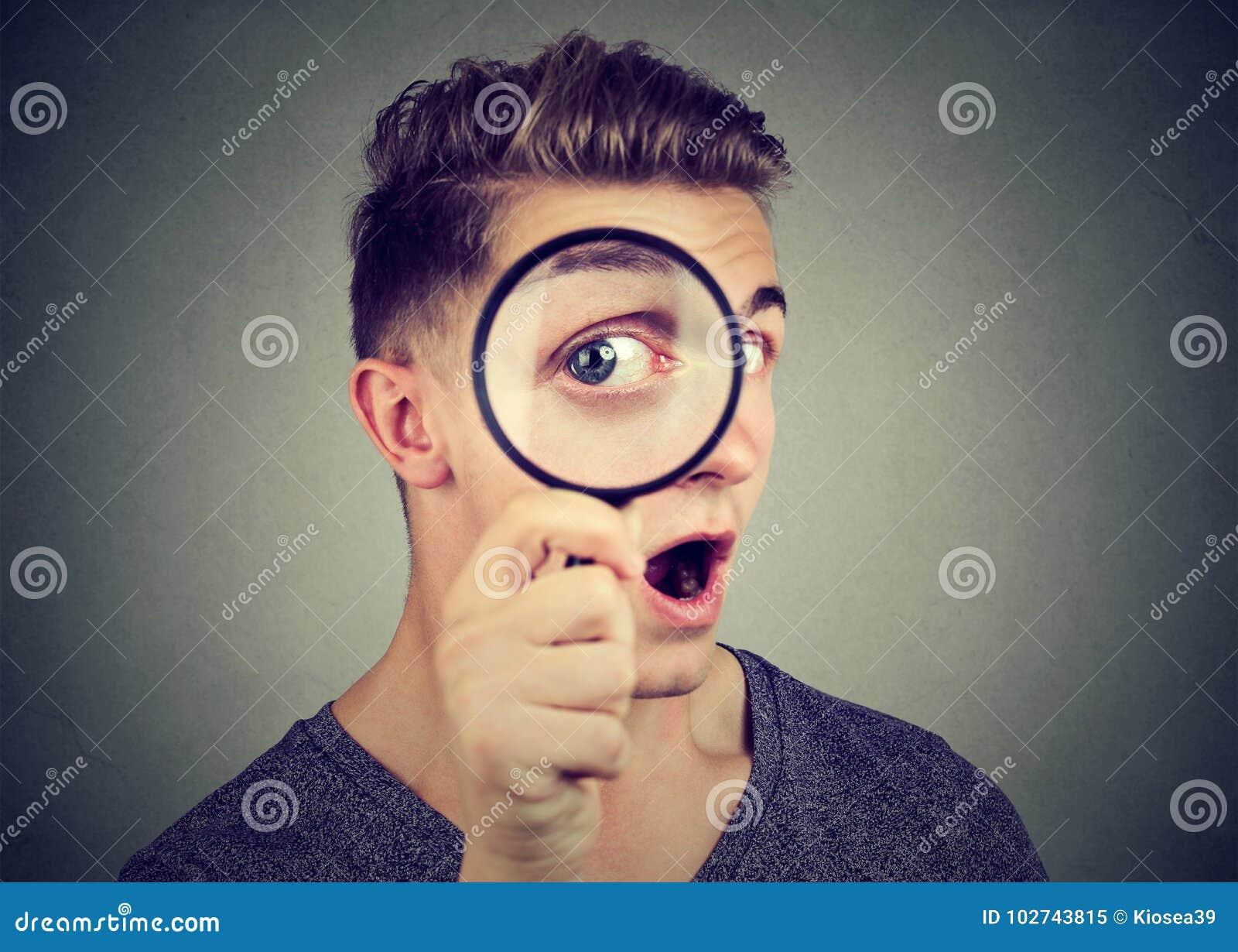 Nyfiken ung man som ser till och med ett förstoringsglas
