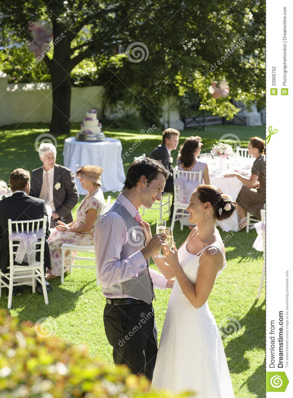 Nygift personpar som rostar Champagne Among Wedding Guests