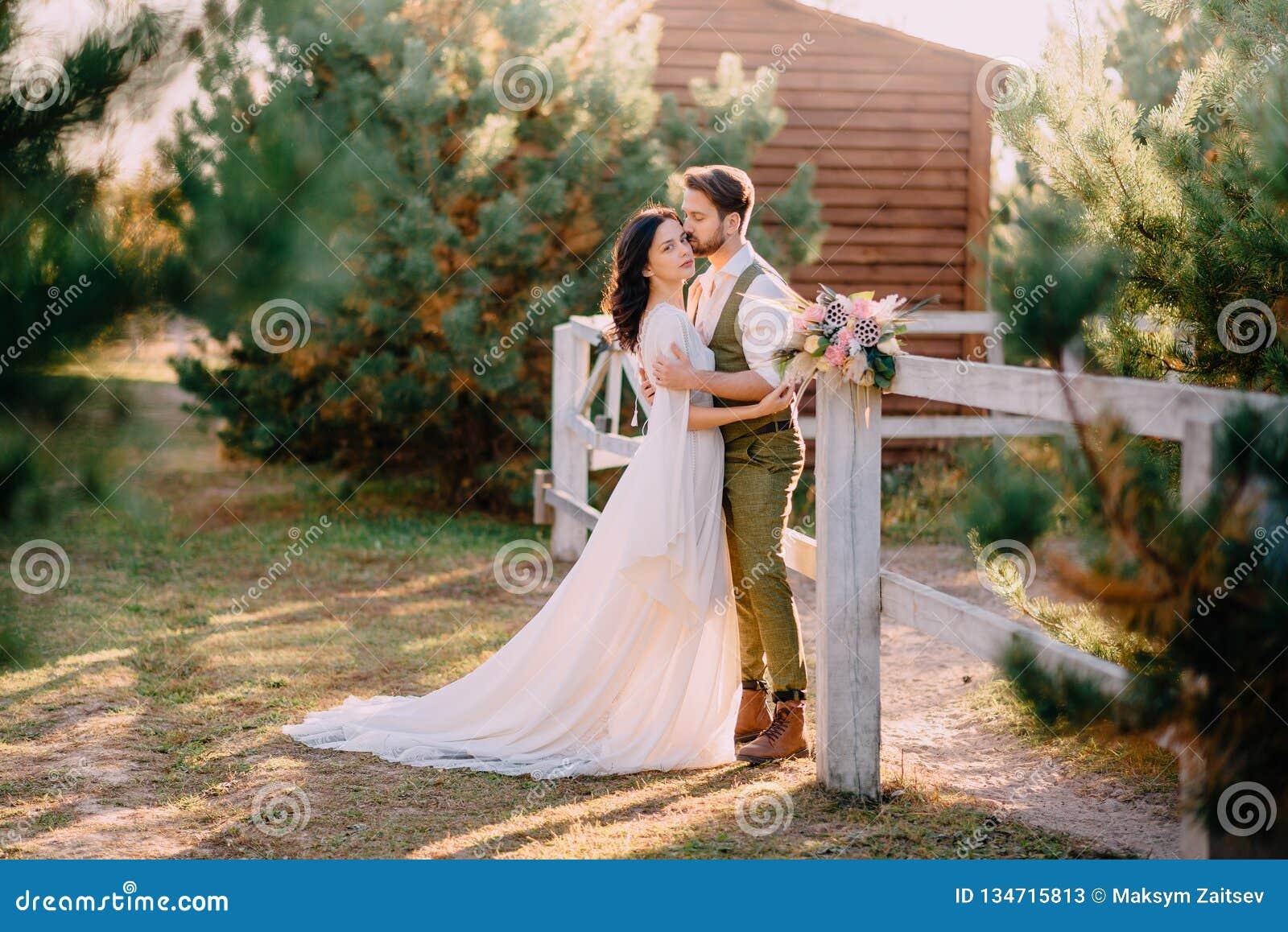 Nygifta personer i cowboystil som står och kramar på ranch