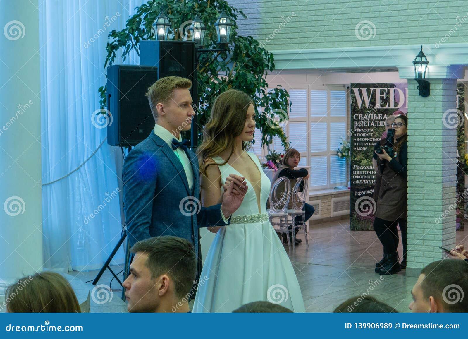 Nyligen modeller för ett gift par som förbigår ett podium