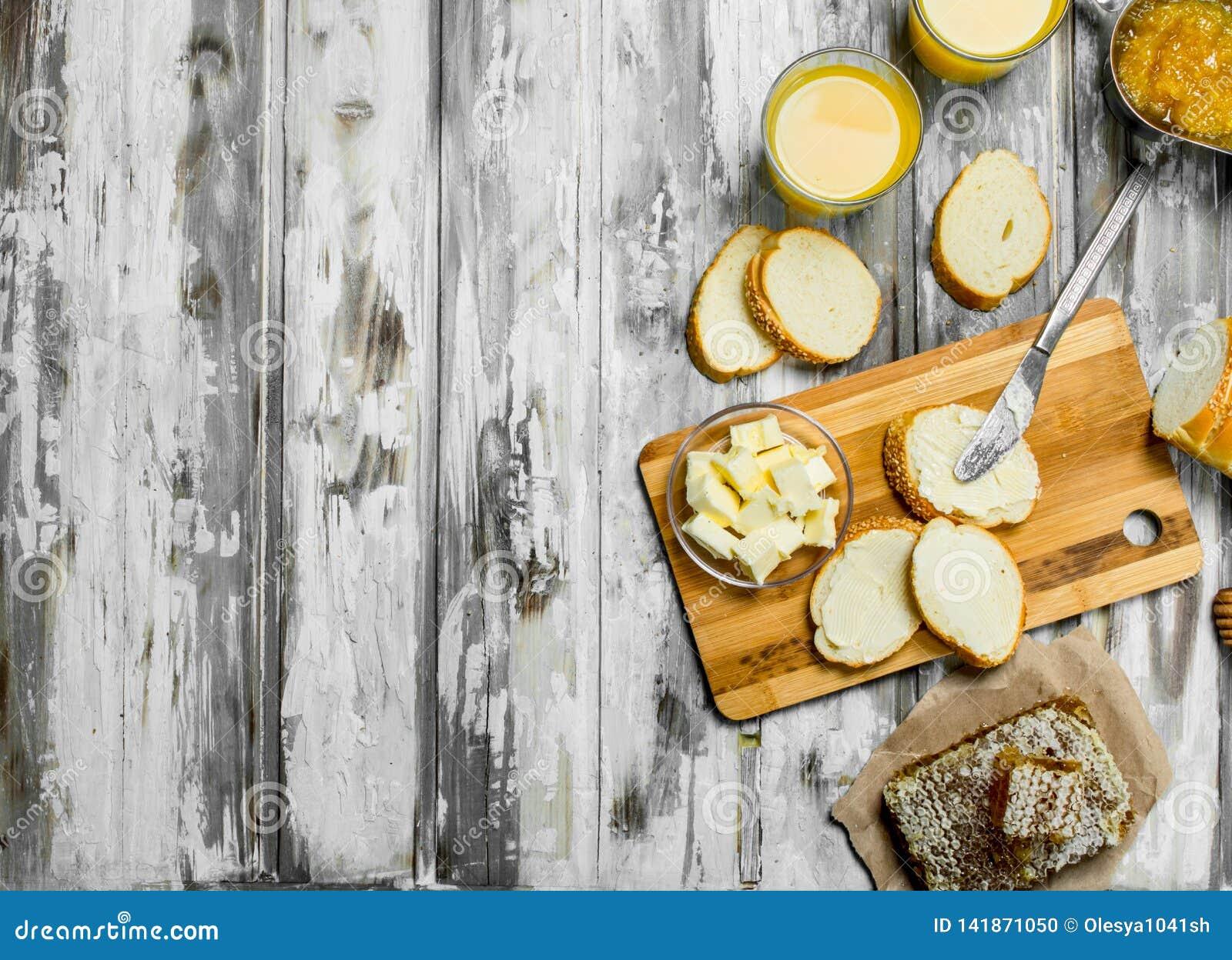Nytt bröd med smör och orange fruktsaft