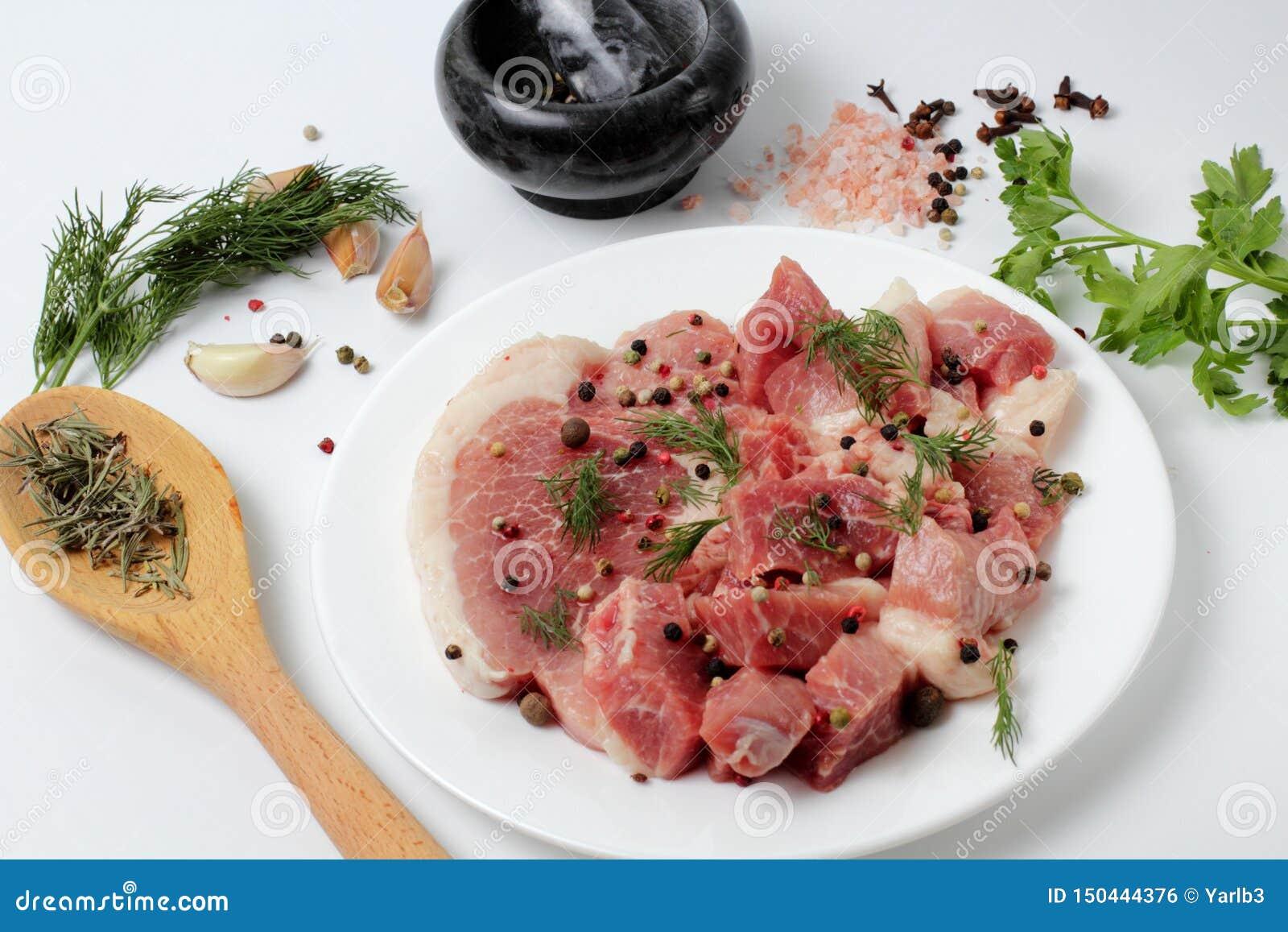 Nytt griskött på en stor platta, kryddor, kryddiga örter