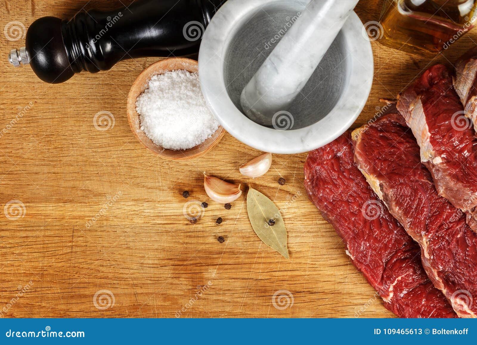 Nytt kött med kryddor på träbräde