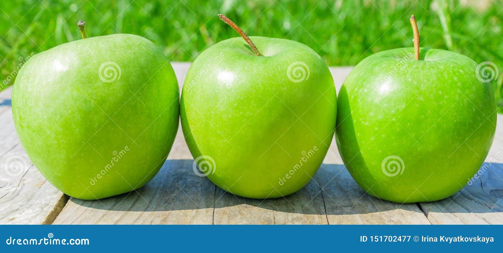 Nytt kantjusterat geen äpplen på trätabellen över grön bakgrund, baner