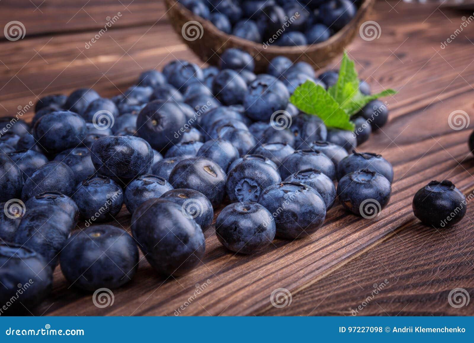 Nytt och ljust blåbär i en träspjällåda, närbild Sunt, moget, rått och ljust mörker - blåa bär på en träbakgrund