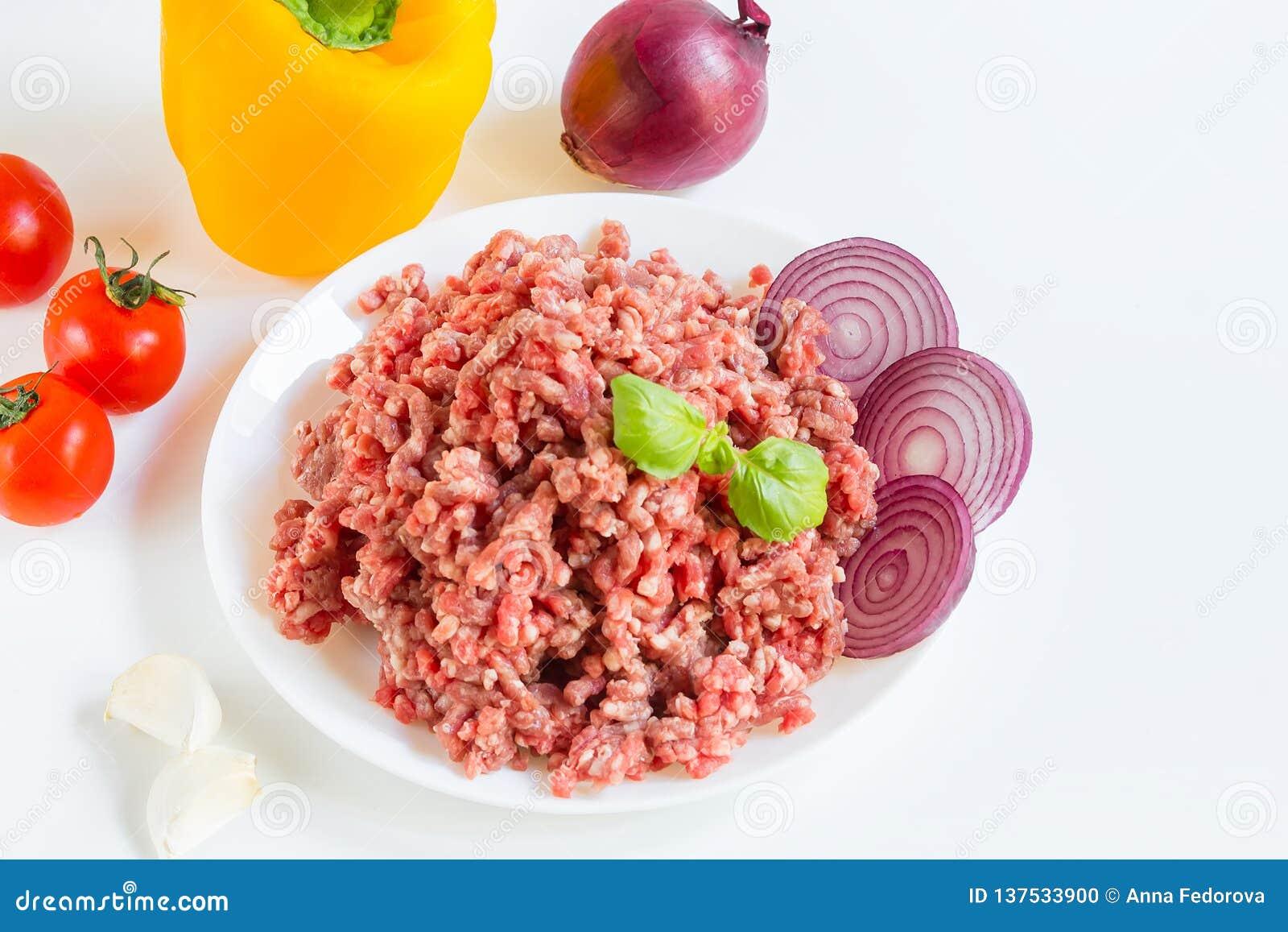 Nytt rått finhackat nötkött i ett vitt plattaslut upp med peppar, löken och tomater, rå ingredienser