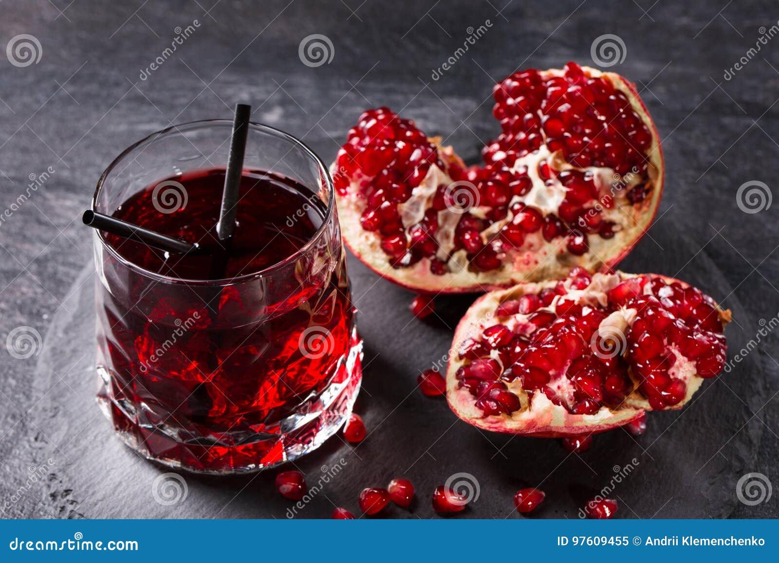Nytt sammanpressad granatäpplefruktsaft med sugrör på en grå bakgrund Mogen, saftig, organisk och fördelgranatröttfrukt