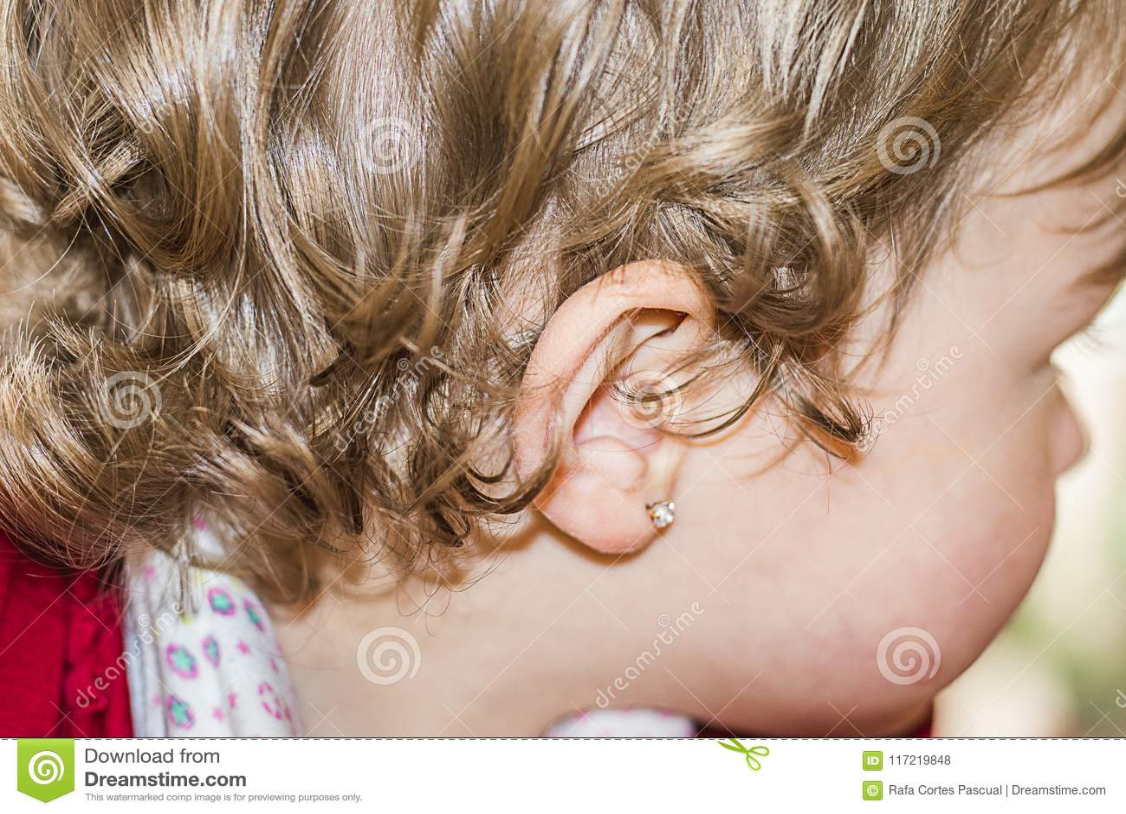 Oído de una niña con un pendiente