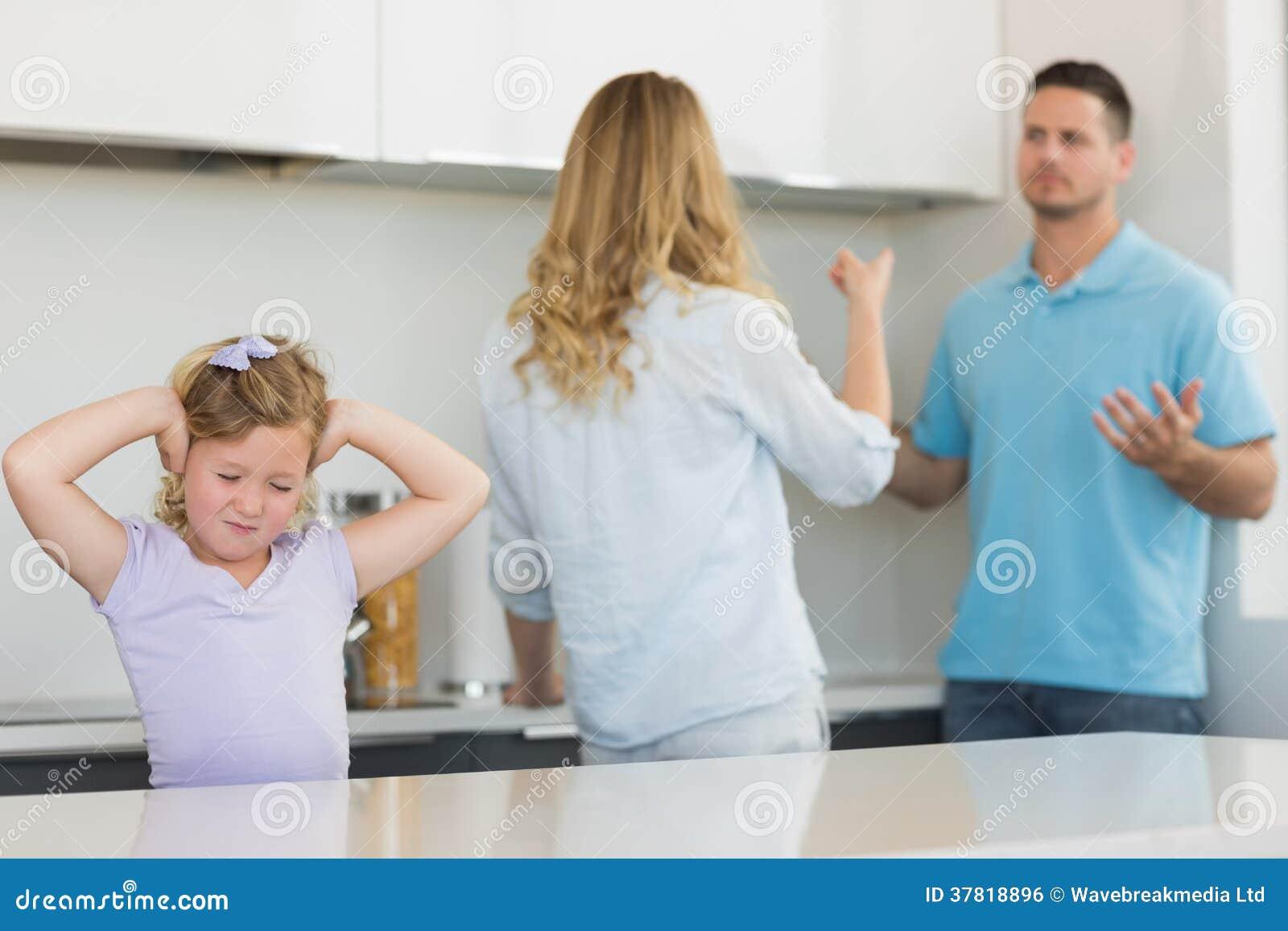 Oídos de la cubierta de la muchacha mientras que discusión de los padres