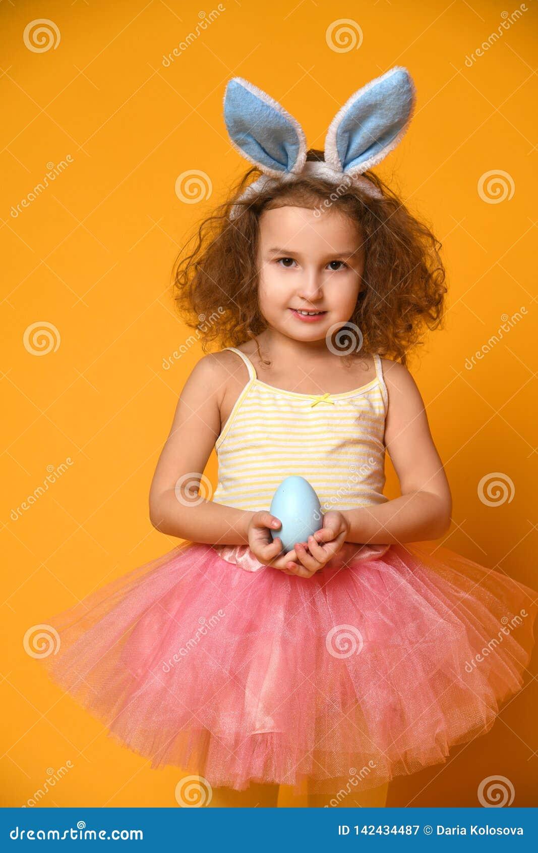 Oídos del conejito de la muchacha linda del pequeño niño que llevan el día de Pascua