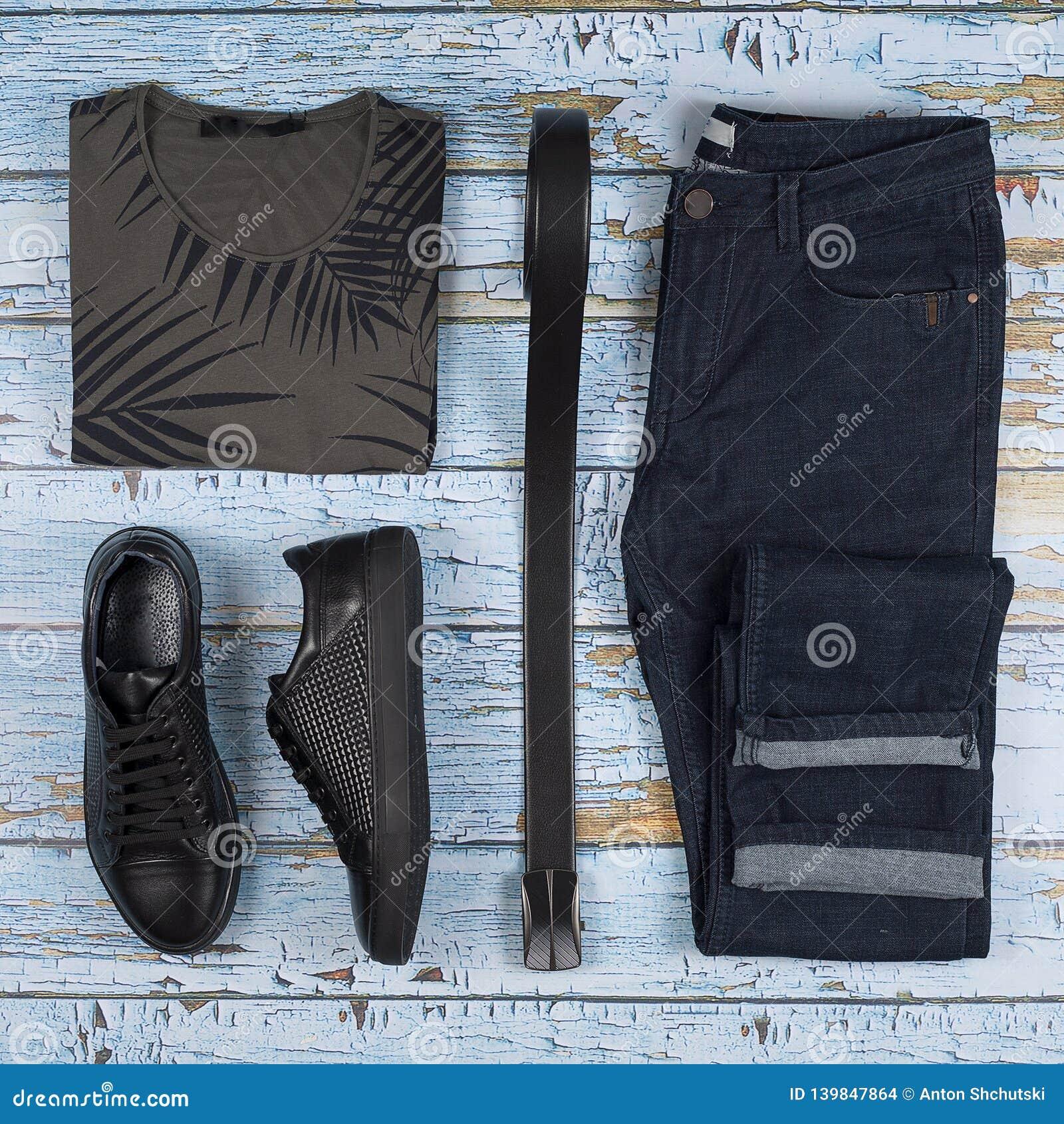 Обмундирования ` s людей вскользь Ботинки, одежда и аксессуары людей на деревянной предпосылке - футболке, джинсах, тапке, поясе