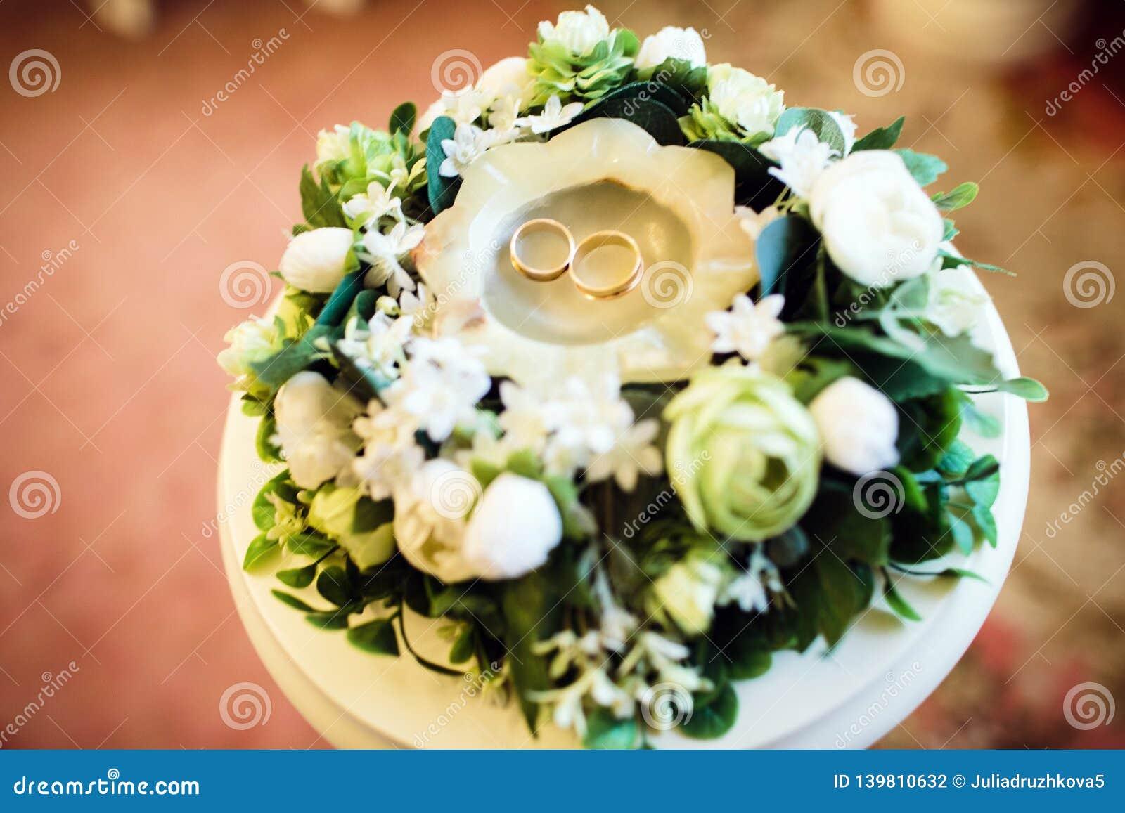 Обручальные кольца в свече среди цветков, букете свадьбы