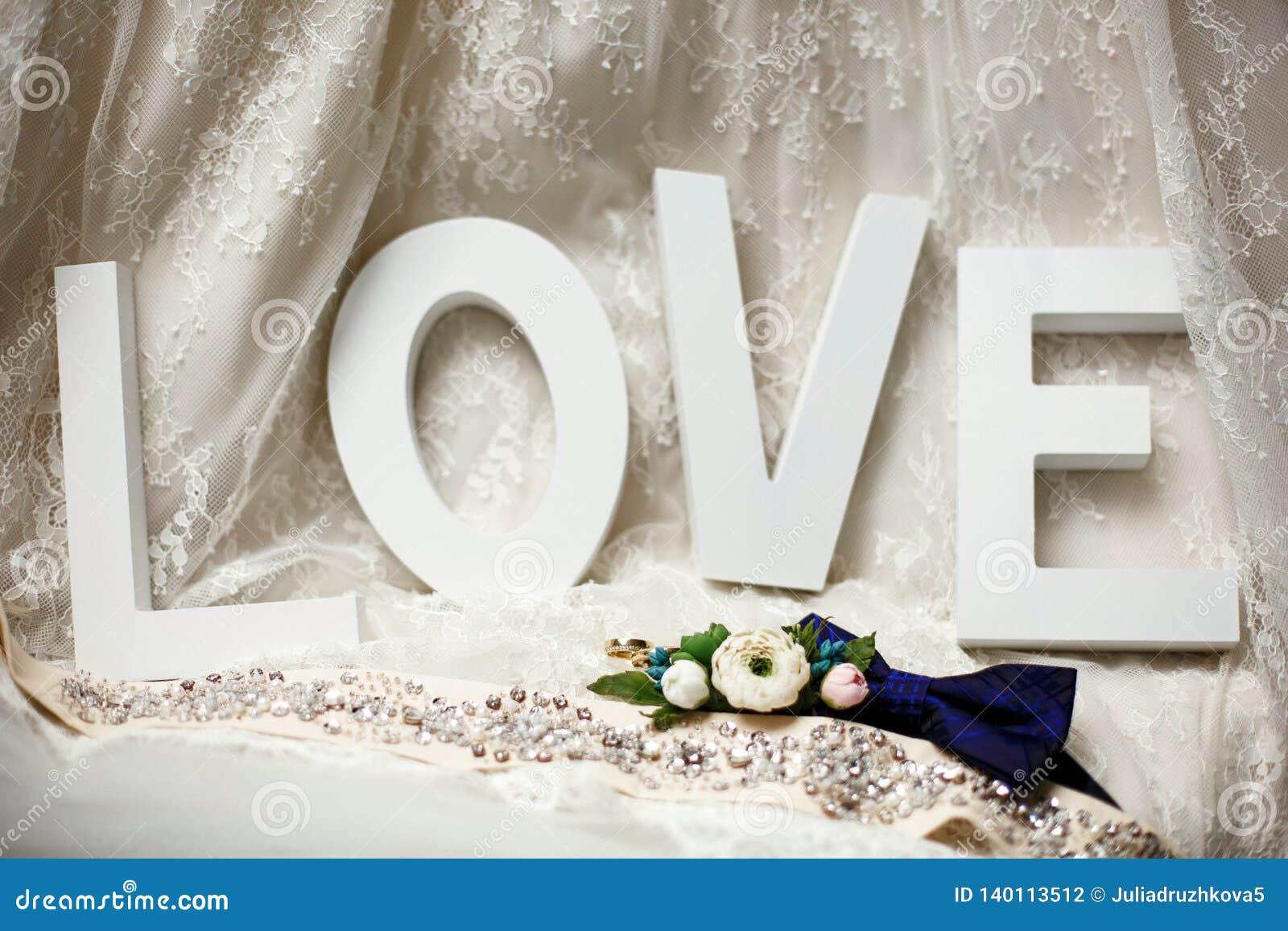 Обручальные кольца лежат перед любовью слова