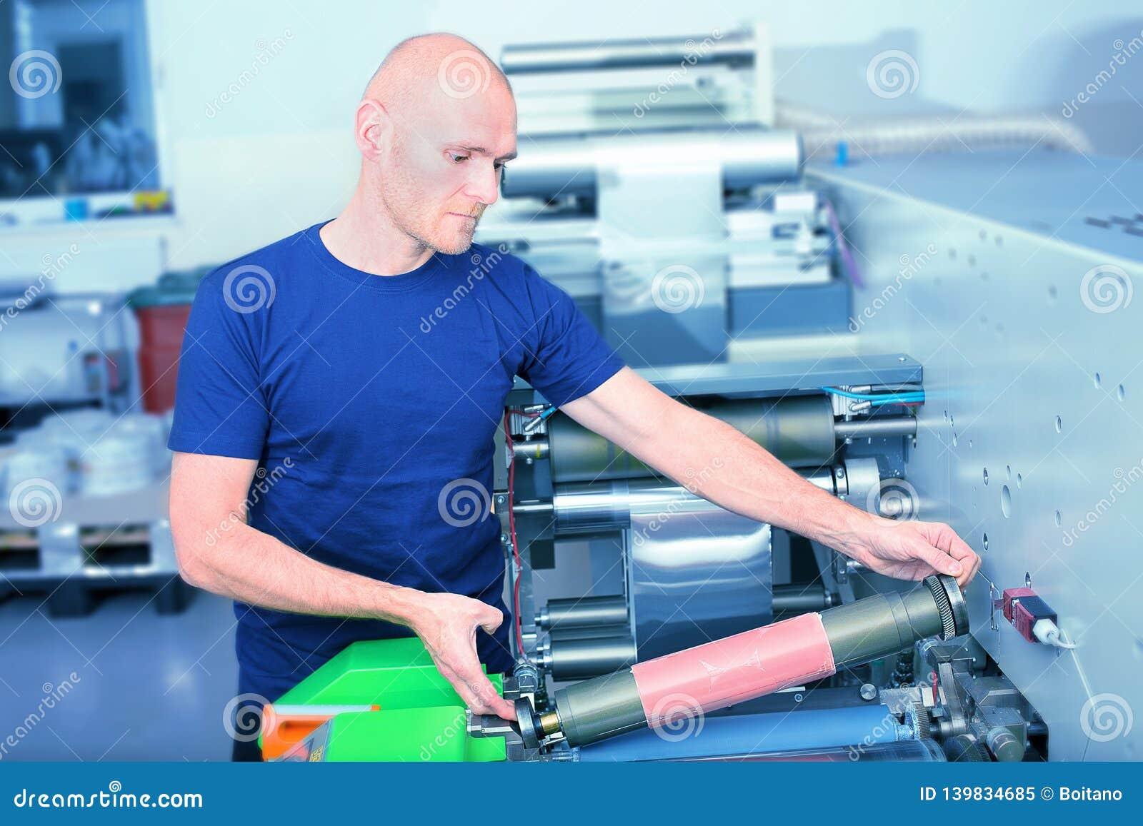 Оператор принтера рядом с печатной машиной, держа печать цилиндра с плитой сброса полимера вставленной на ей