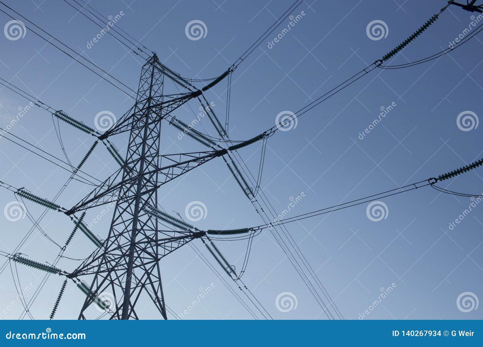 Опоры электропитания против голубого неба