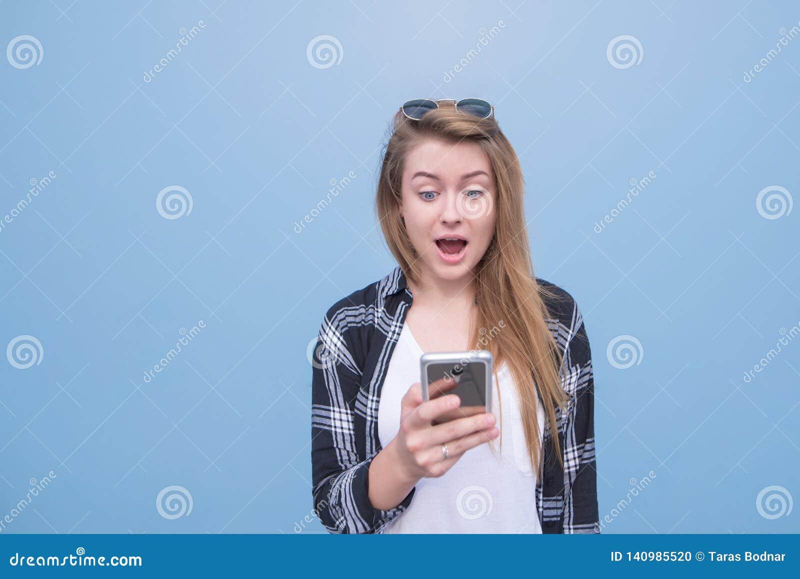Одежды эмоциональной девушки случайные с удивленными глазами смотря смартфон в руках на голубой предпосылке