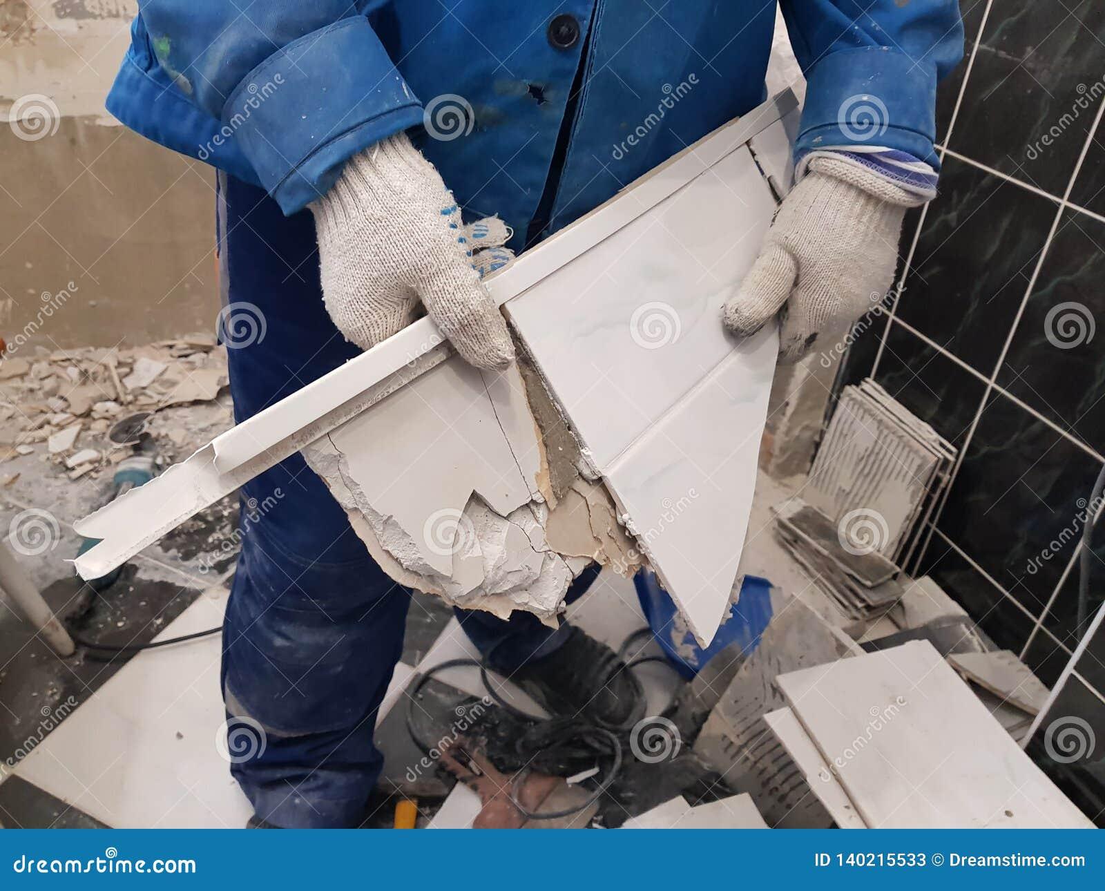 Отход конструкции и старая плитка в руке