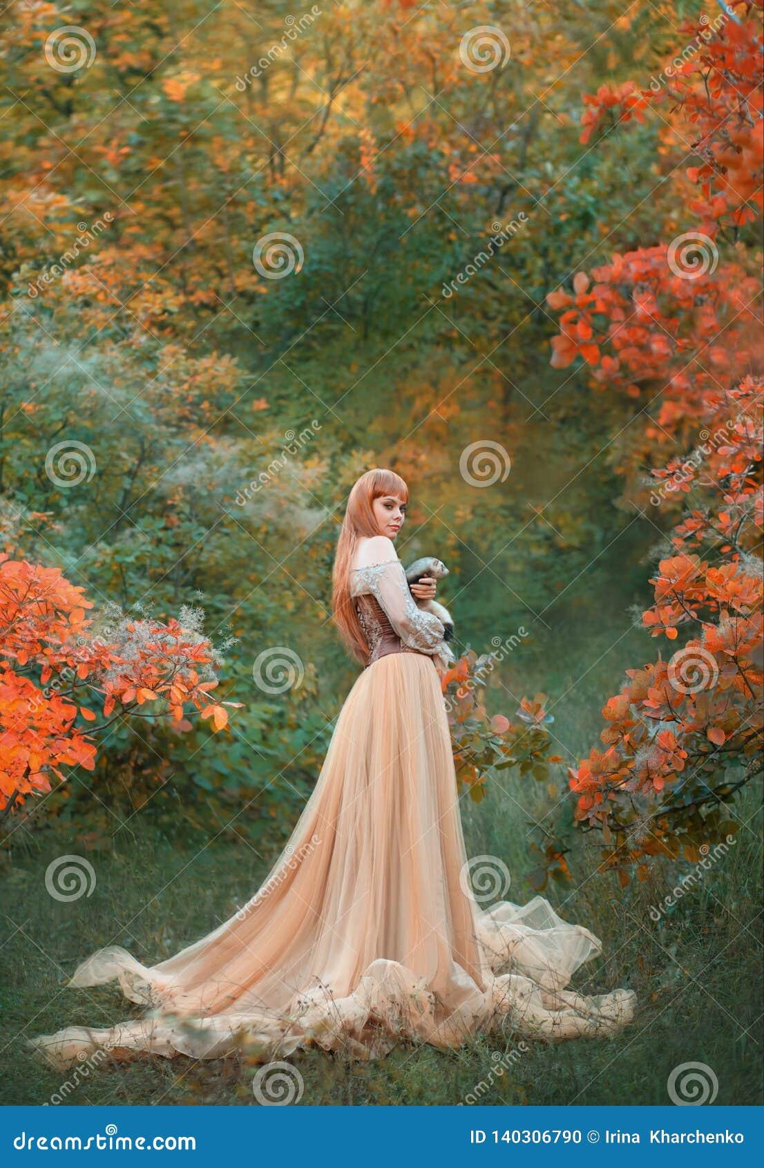 Очаровывая шикарная девушка с пламенистыми красными волосами стоит самостоятельно в лесе осени в длинном светлом шикарном платье