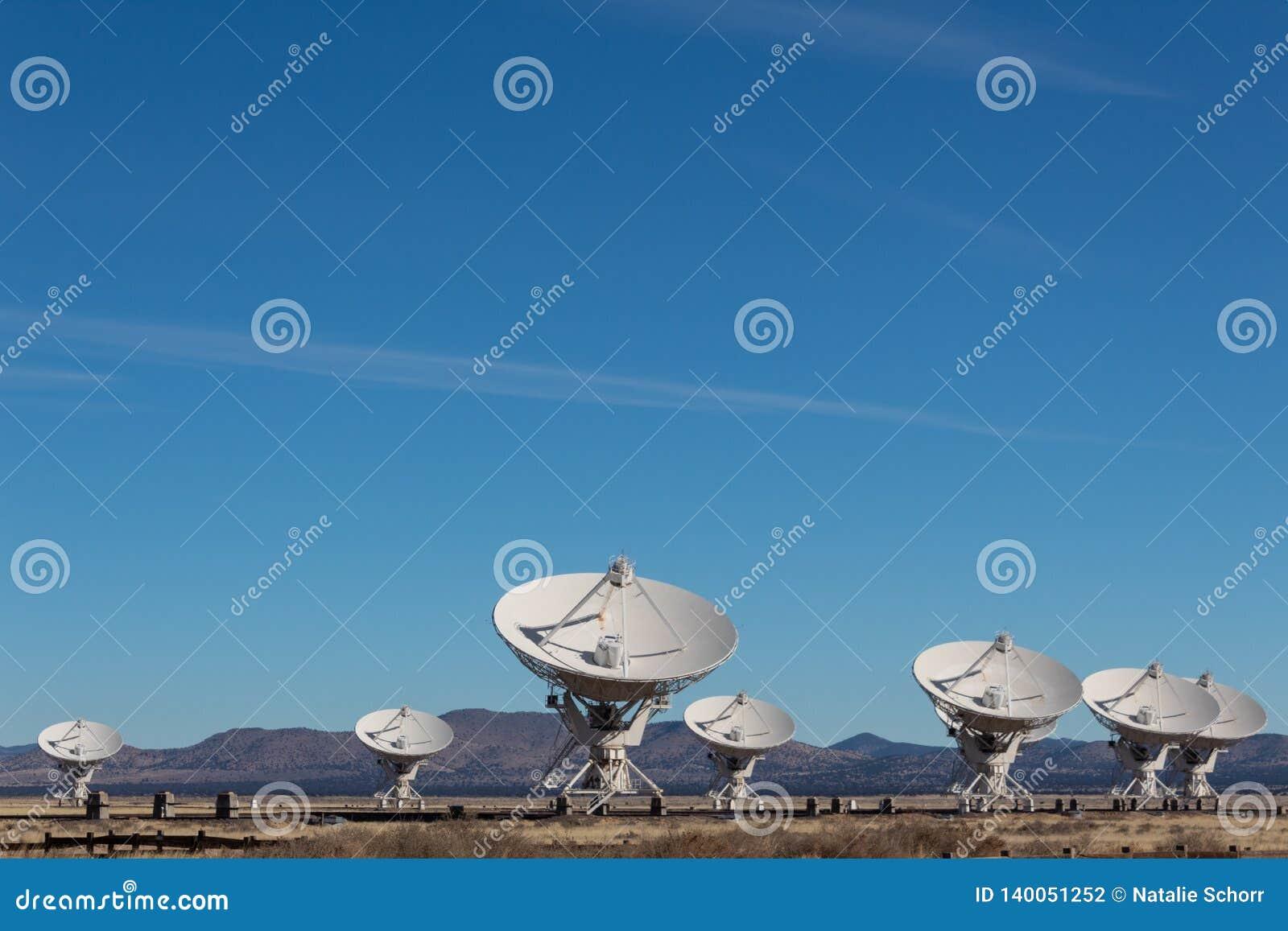 Очень большая группа в составе массива тарелки антенны радио в пустыне Неш-Мексико, голубом небе