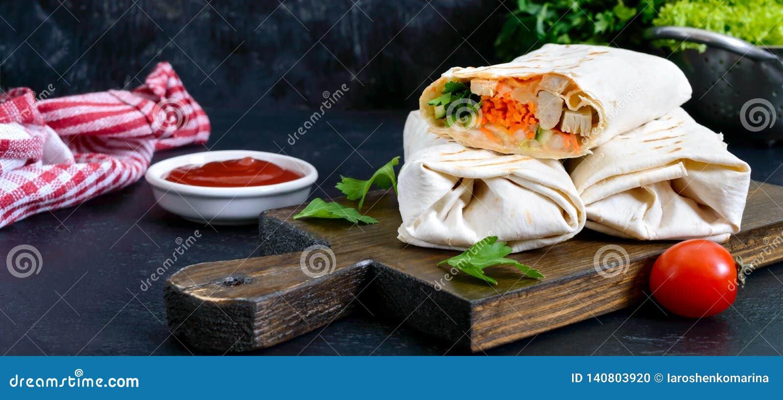 Очень вкусный сэндвич shawarma на черной предпосылке Обручи буррито с зажаренными цыпленком и овощами, зелеными цветами