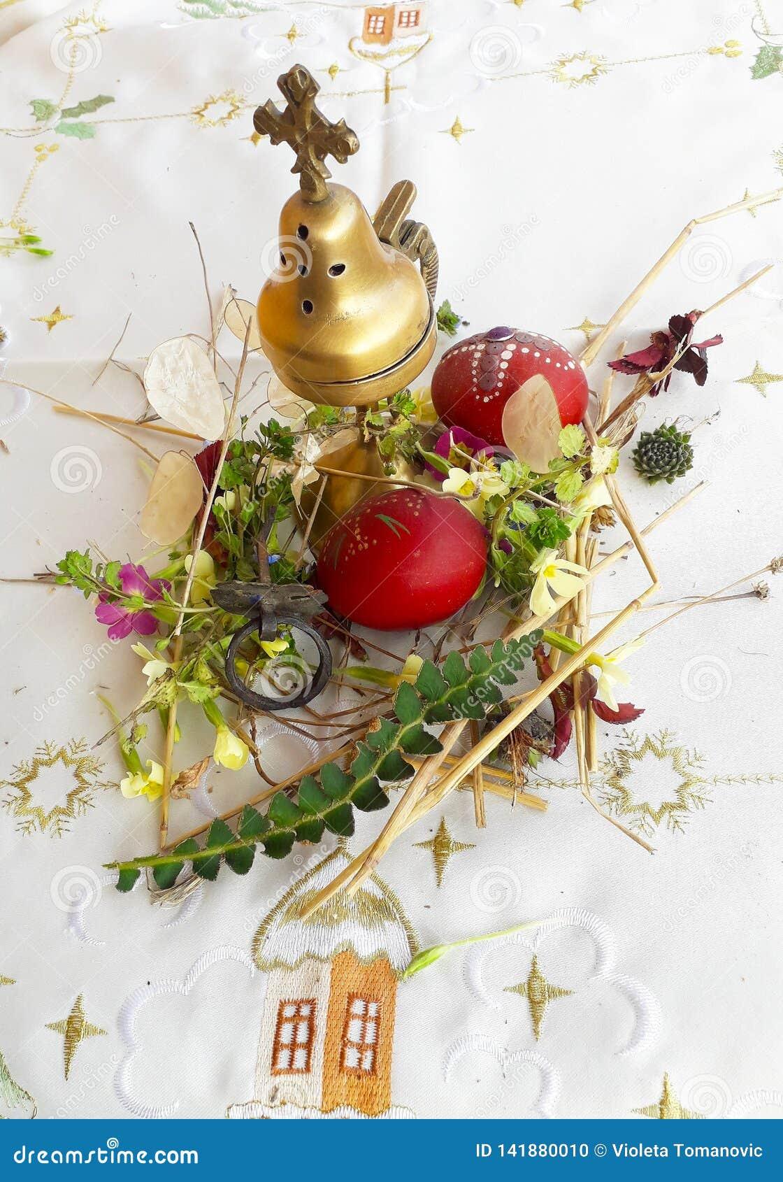 Орнаментированное красное пасхальное яйцо со свежими полевыми цветками и травами