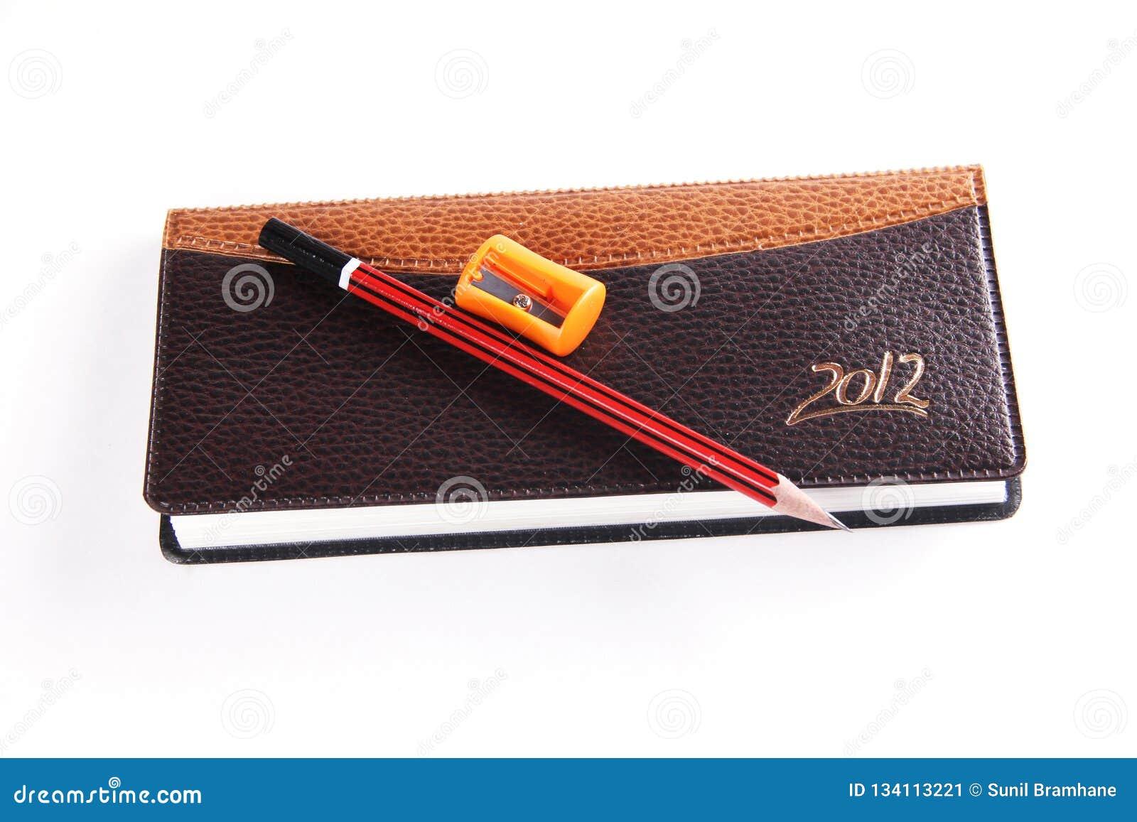 Ołówkowej ostrzarki i notatnika nabiał odizolowywający na białym tle