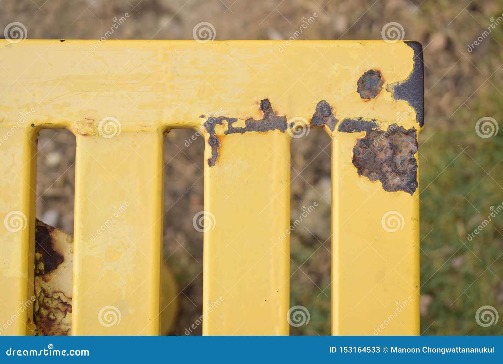 Ośniedziała żółta ławka w parku