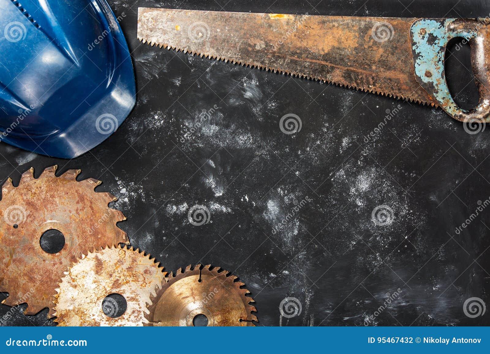 Ośniedziała kurenda zobaczył ostrza, saw i zbawczego hełm na zmroku kamienia tle,