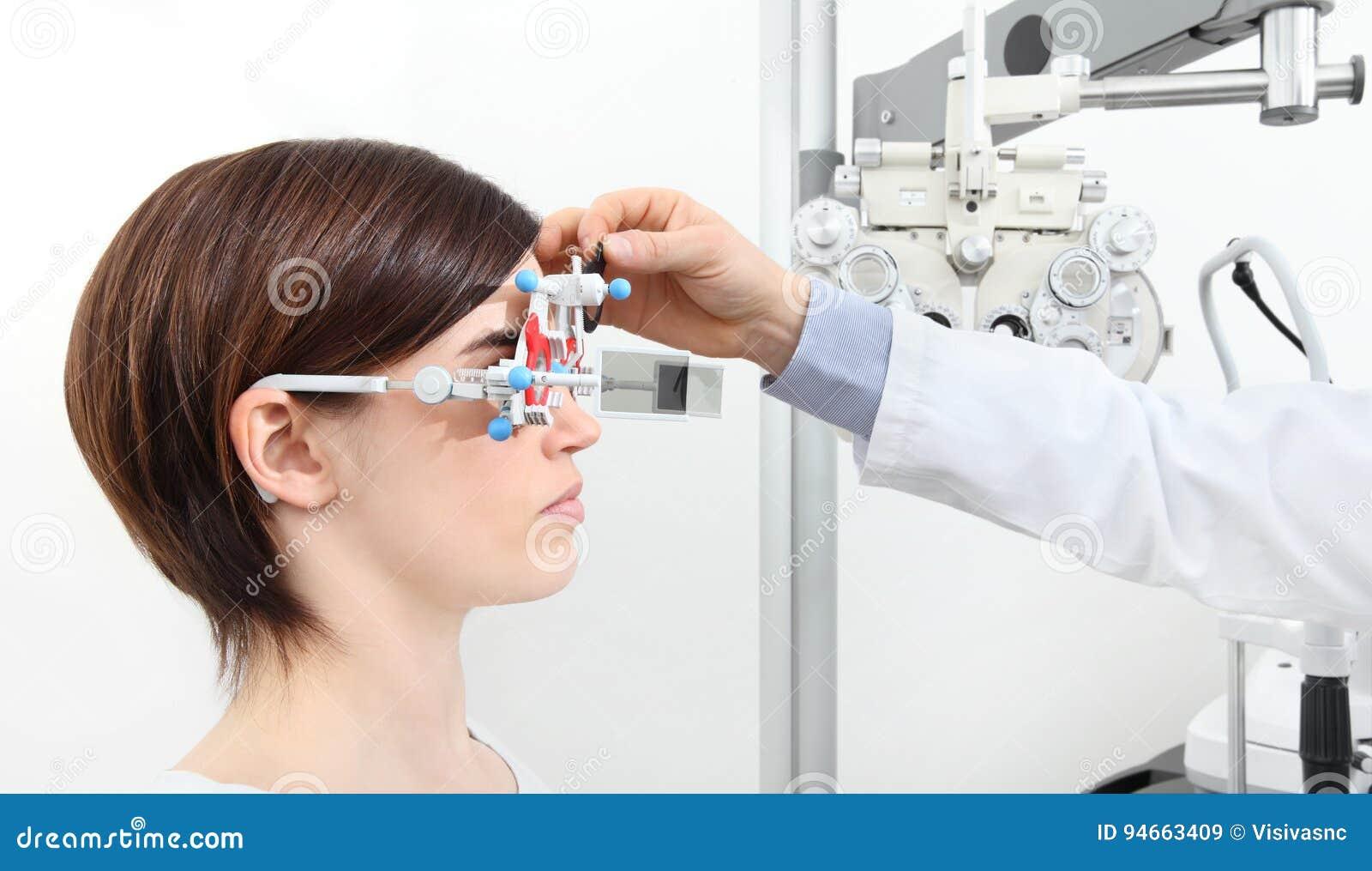 O ótico com quadro experimental, doutor do optometrista examina a visão