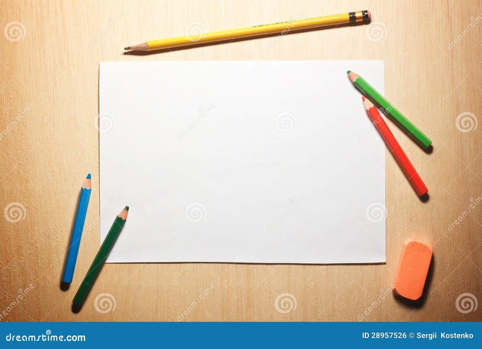 Ołówki i pusty papier na drewnianym stole