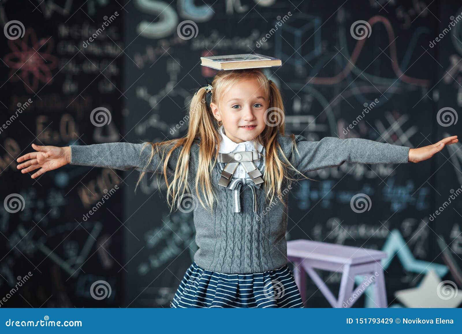 O λίγο ξανθό κορίτσι στο παιδί σχολικών στολών από το δημοτικό σχολείο κρατά τα βιβλία στο κεφάλι της : παιδί με
