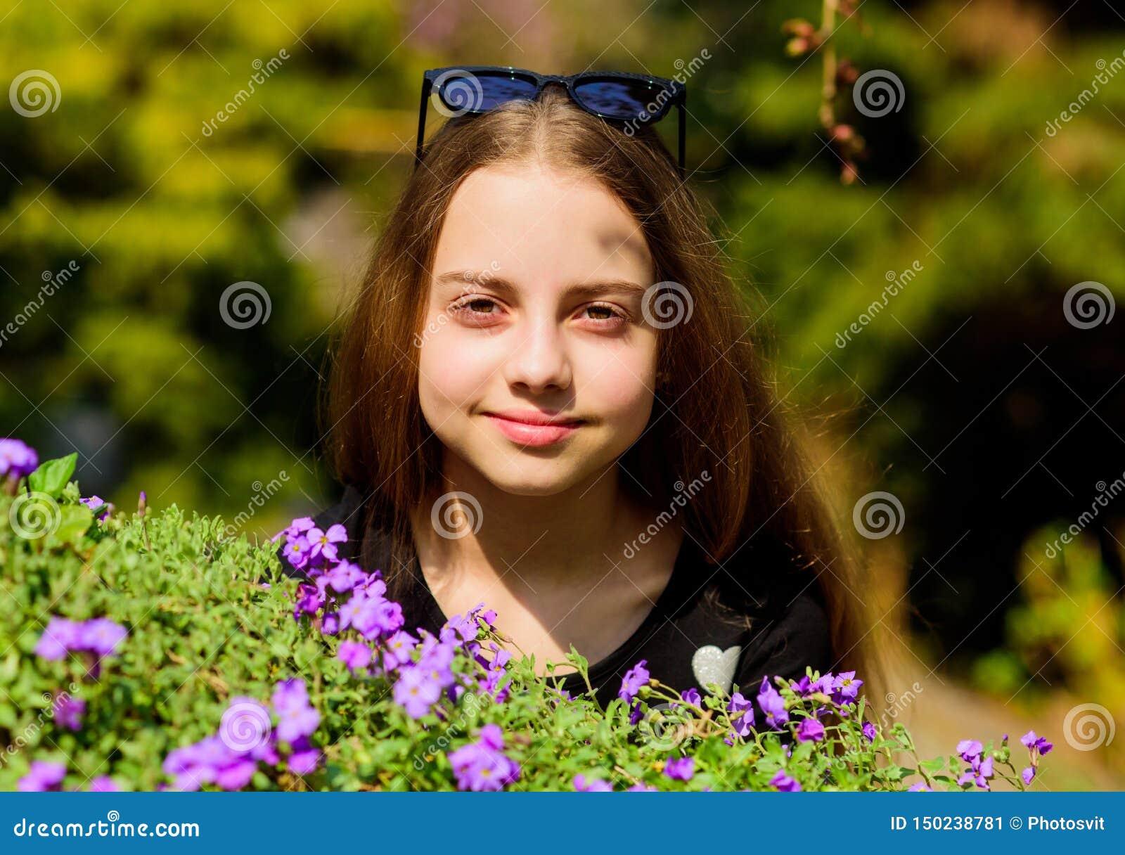 O   цветки запаха маленькой девочки зацветая счастливый ребенок с цветенем куста r