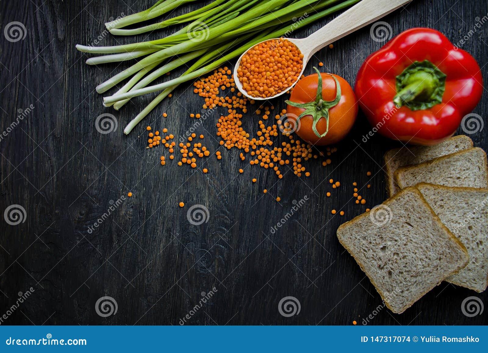 O 平衡的健康吃背景 扁豆,白面包,菜,在一黑暗木的绿色