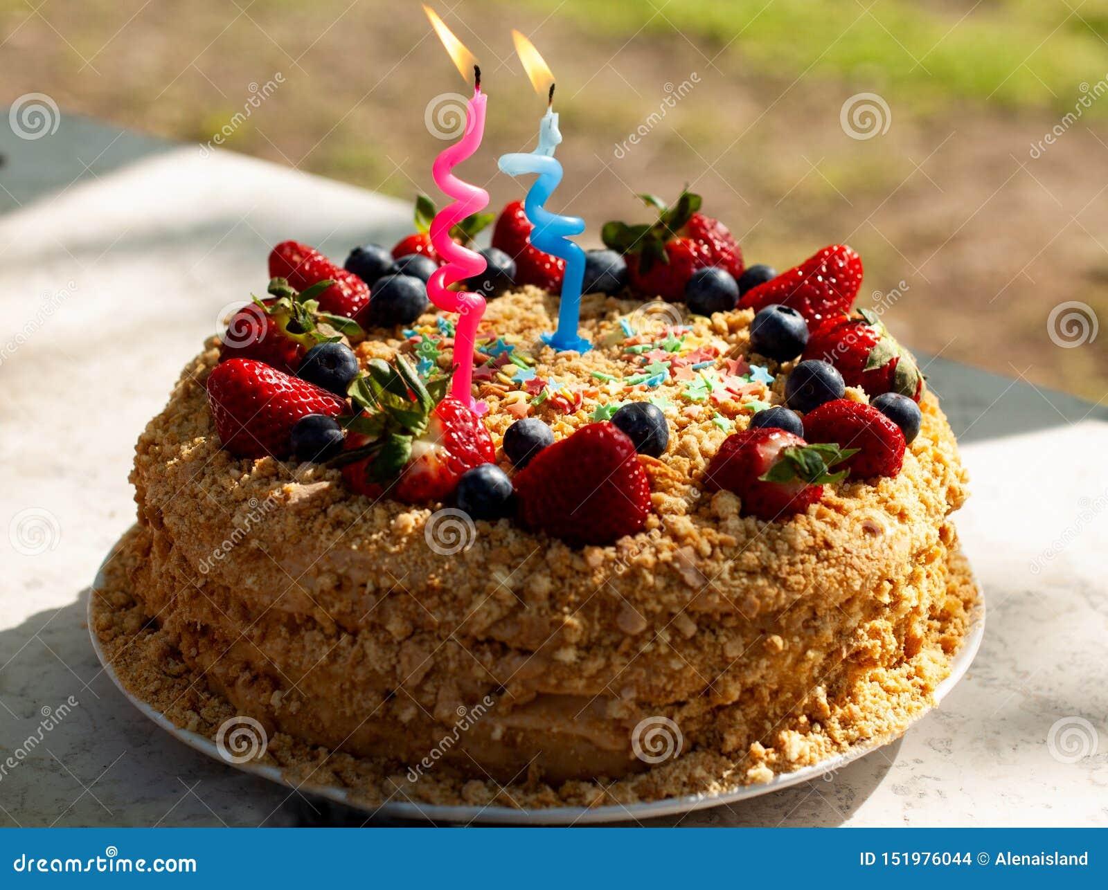 O 用蜡烛为生日装饰的自创蛋糕,新鲜的蓝莓,草莓 ??