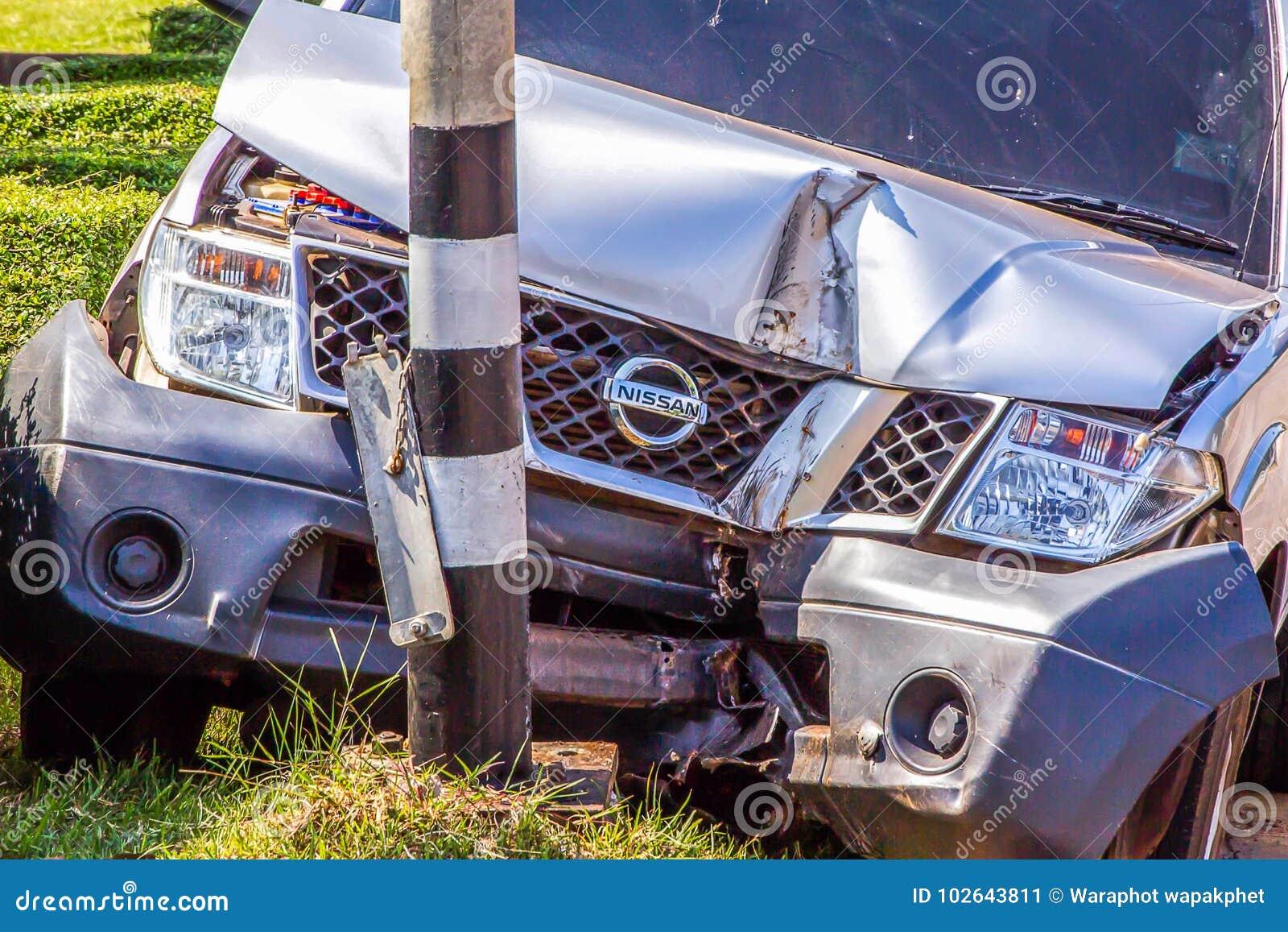 O acidente do camionete de Nissan bateu a lâmpada da borda da estrada no distrito de Muang