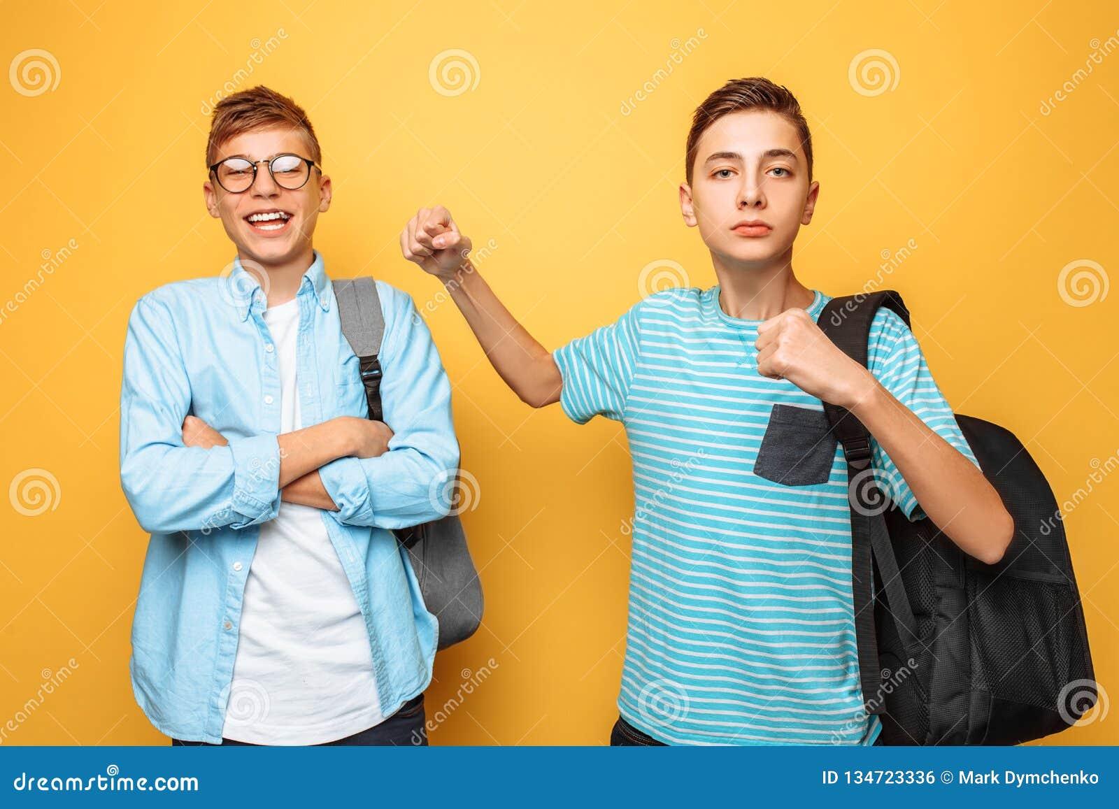 O adolescente ameaça, o irmão impertinente, punho, em um fundo amarelo