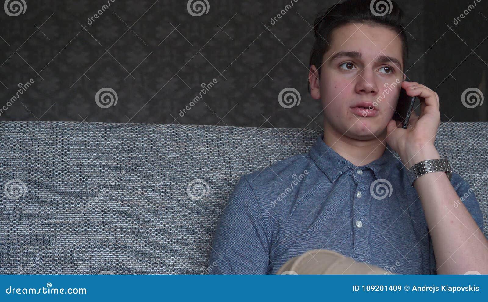 O adolescente considerável do menino que fala no telefone senta-se em um sofá cinzento