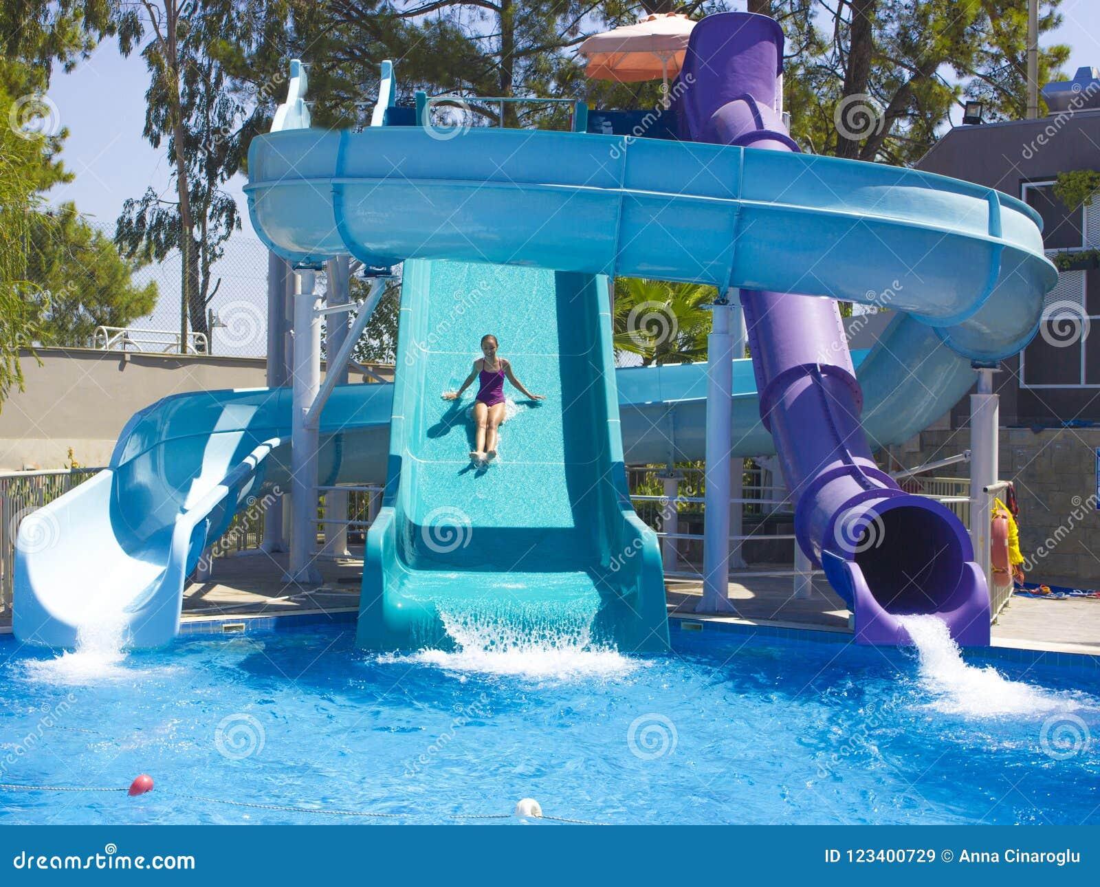 O adolescente feliz que vai para baixo pela água desliza na associação
