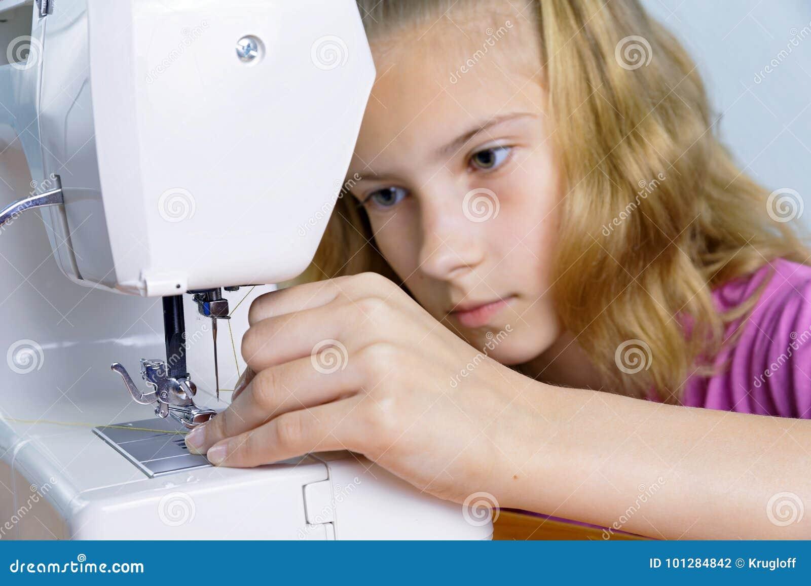 O adolescente introduz com cuidado a linha na agulha