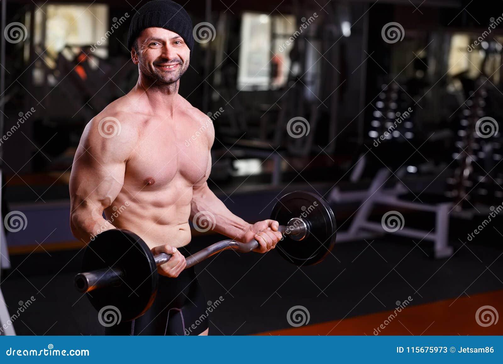 O adulto saudável forte rasgou o homem com músculos grandes que treina com b