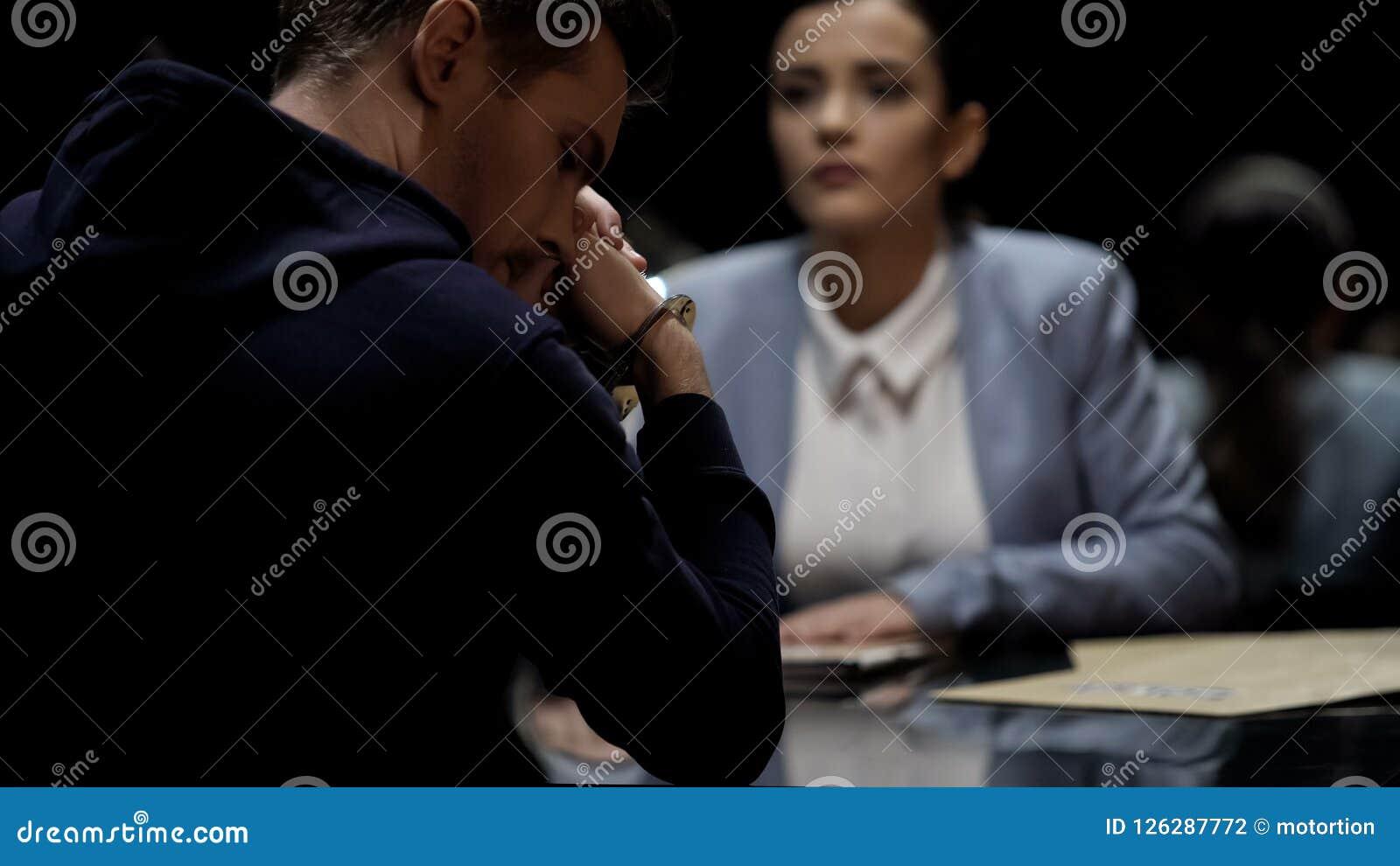 O agente da autoridade que interroga o suspeito de assassinato, homem prendido sente culpado