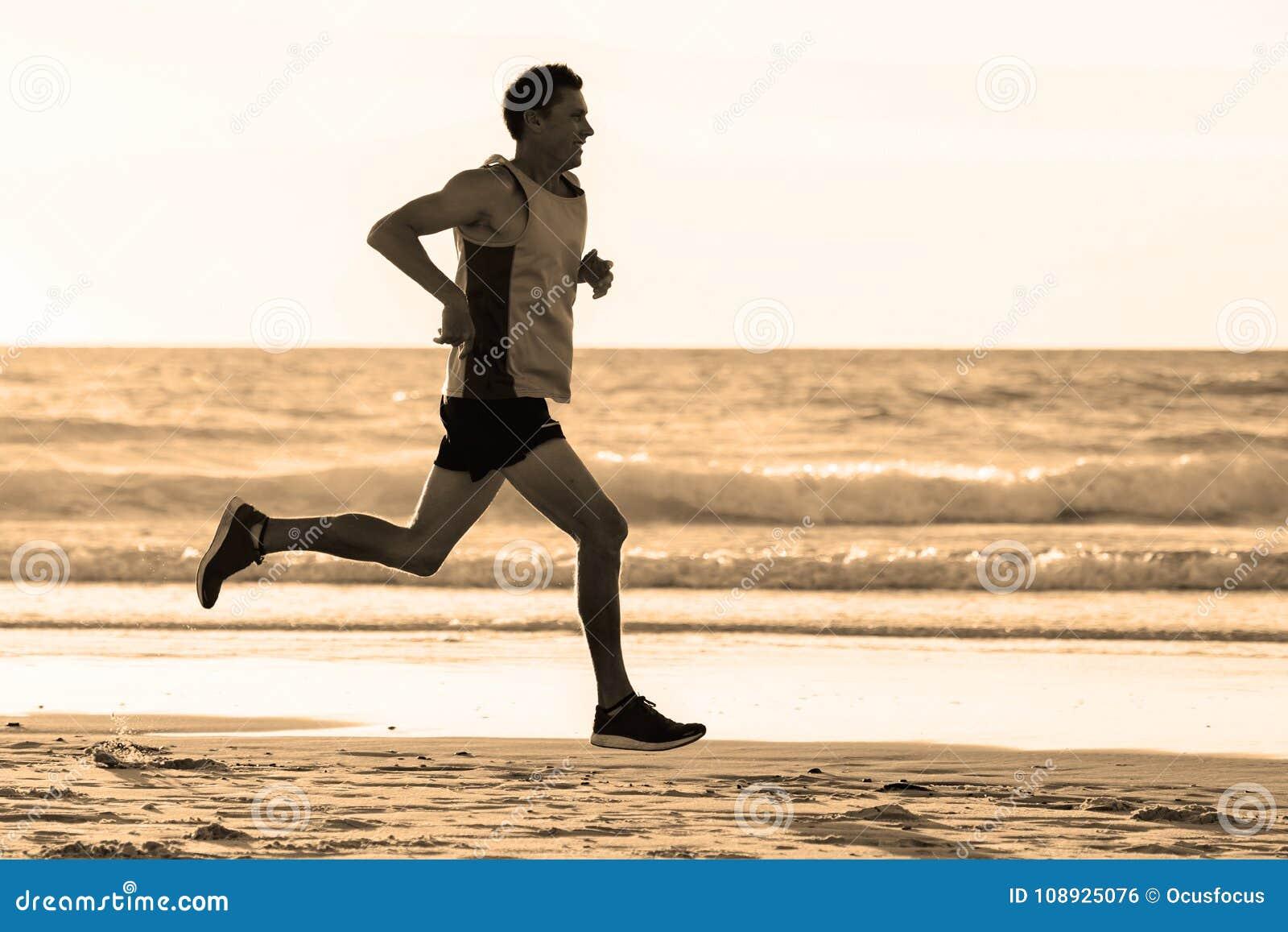 O ajuste atlético e o corredor forte equipam o treinamento na praia do por do sol do verão no corredor da costa de mar e no exerc