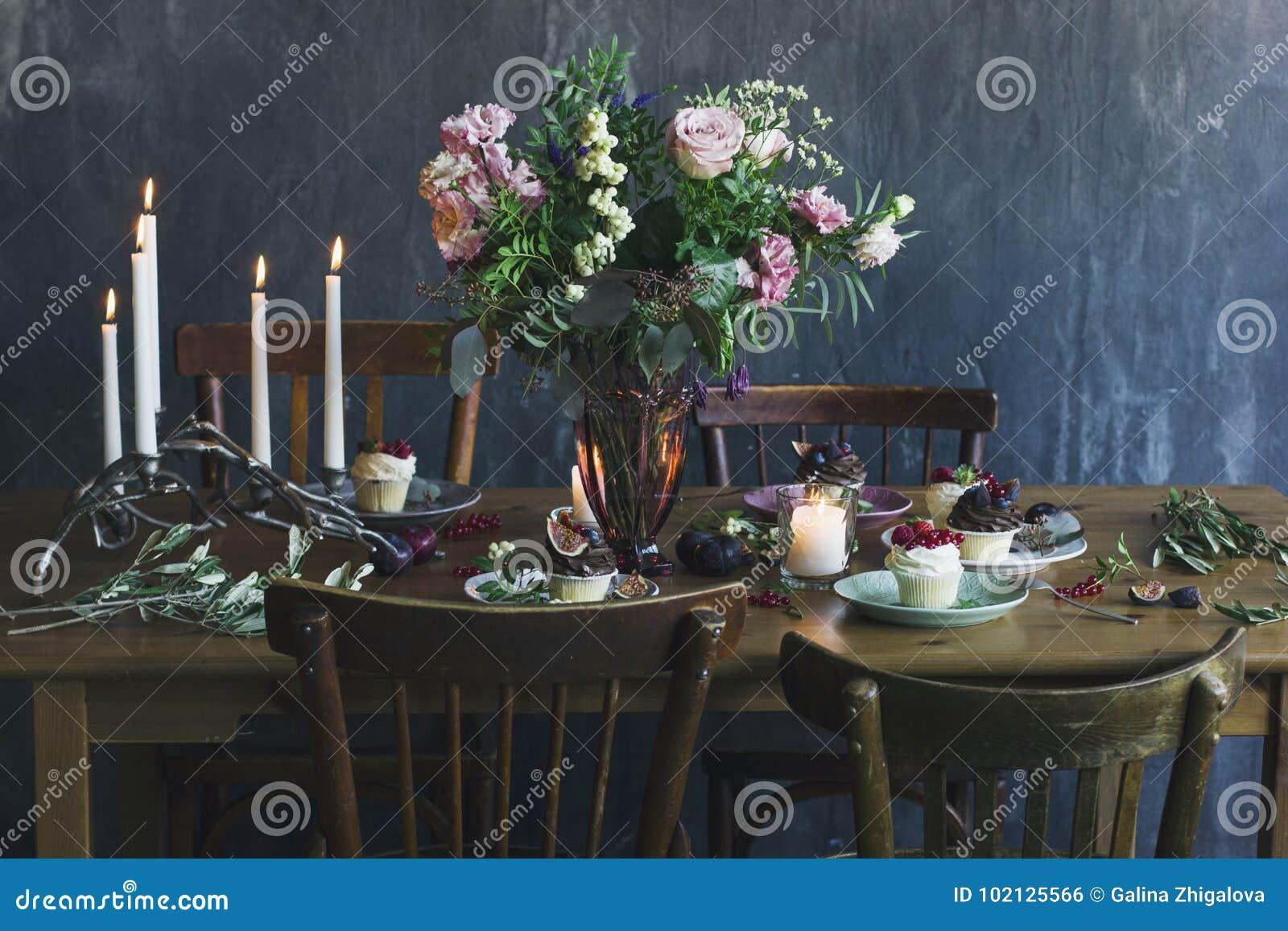 O ajuste festivo da tabela com ramalhete, velas e dess da flor