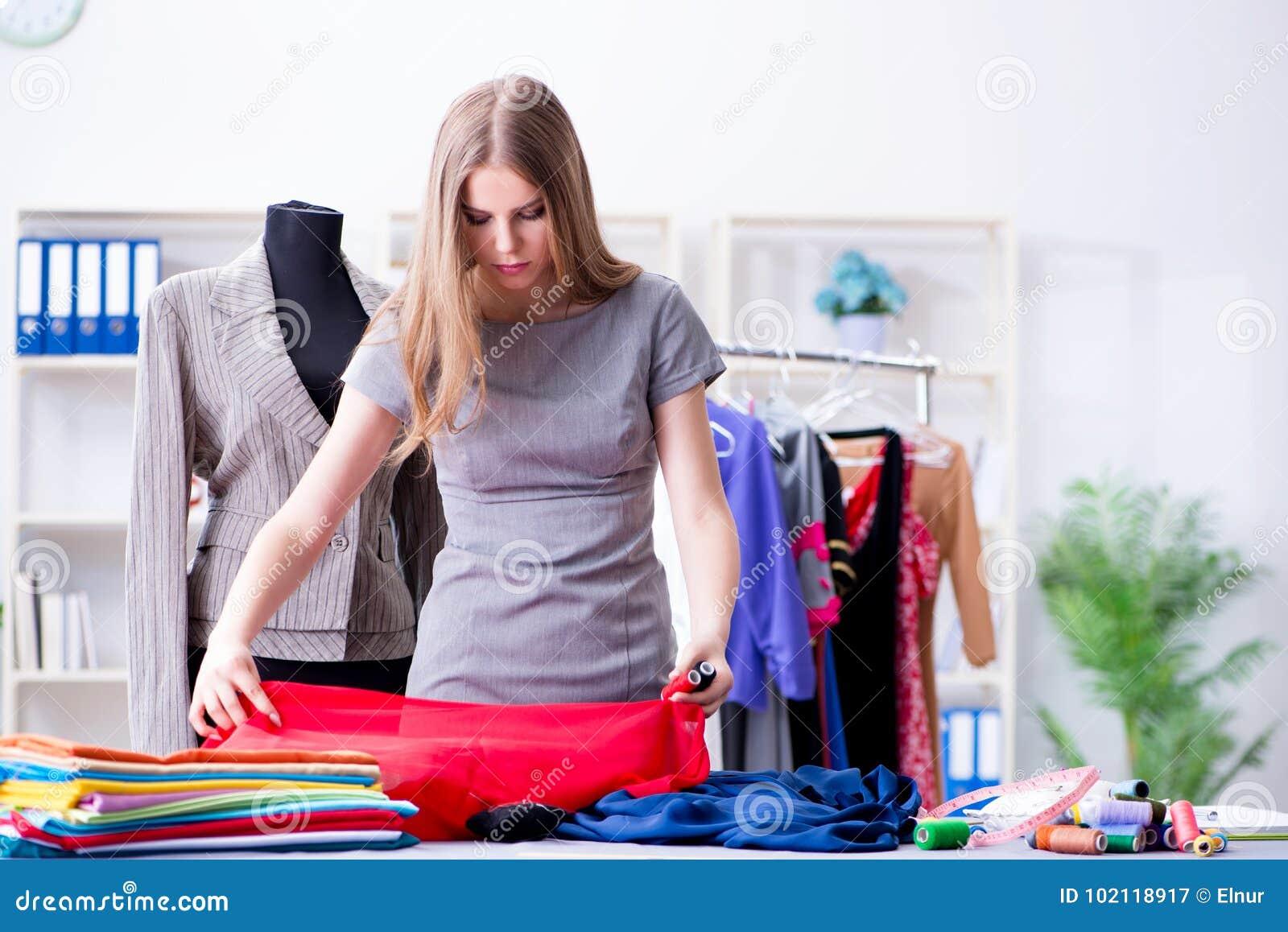 O alfaiate da jovem mulher que trabalha na oficina no vestido novo
