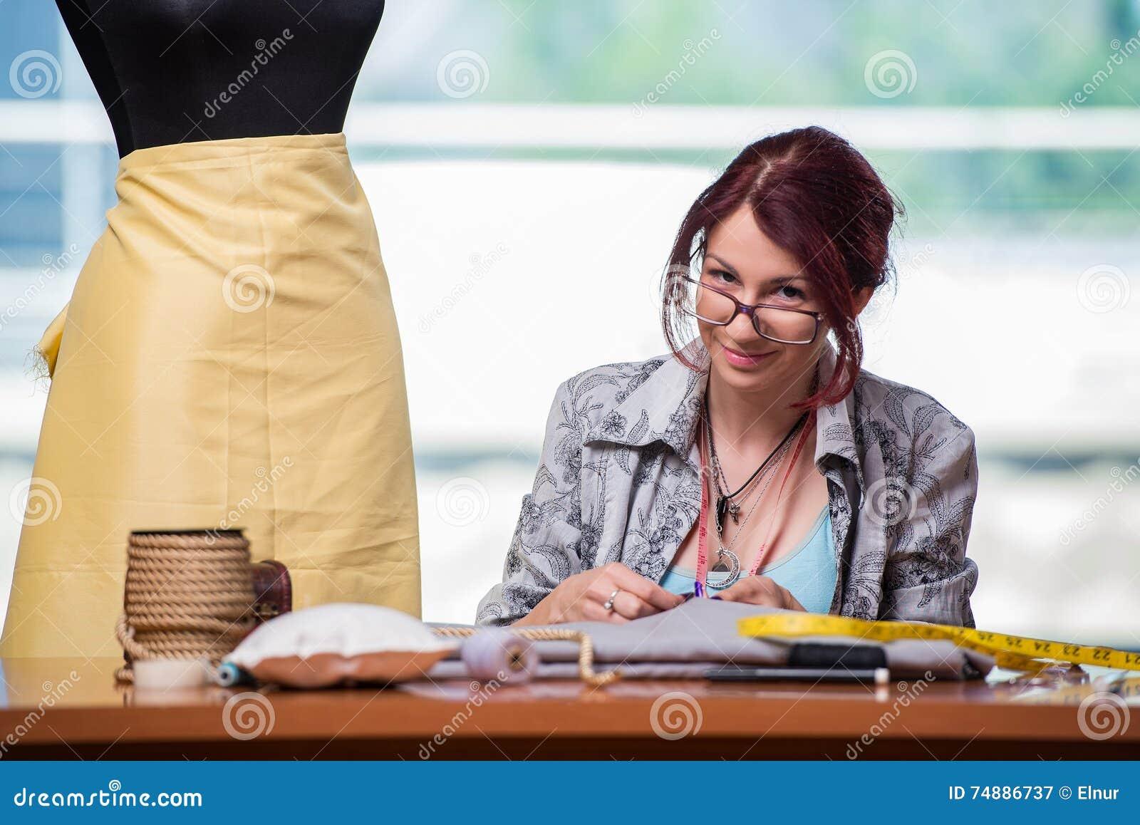 O alfaiate da mulher que trabalha em sua mesa