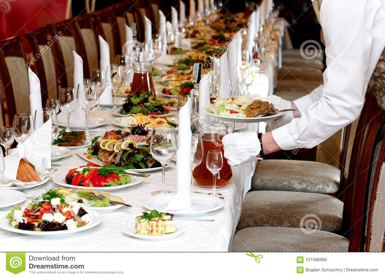 O alimento do serviço do garçom na tabela luxuosa ajustou-se no copo de água, Ca
