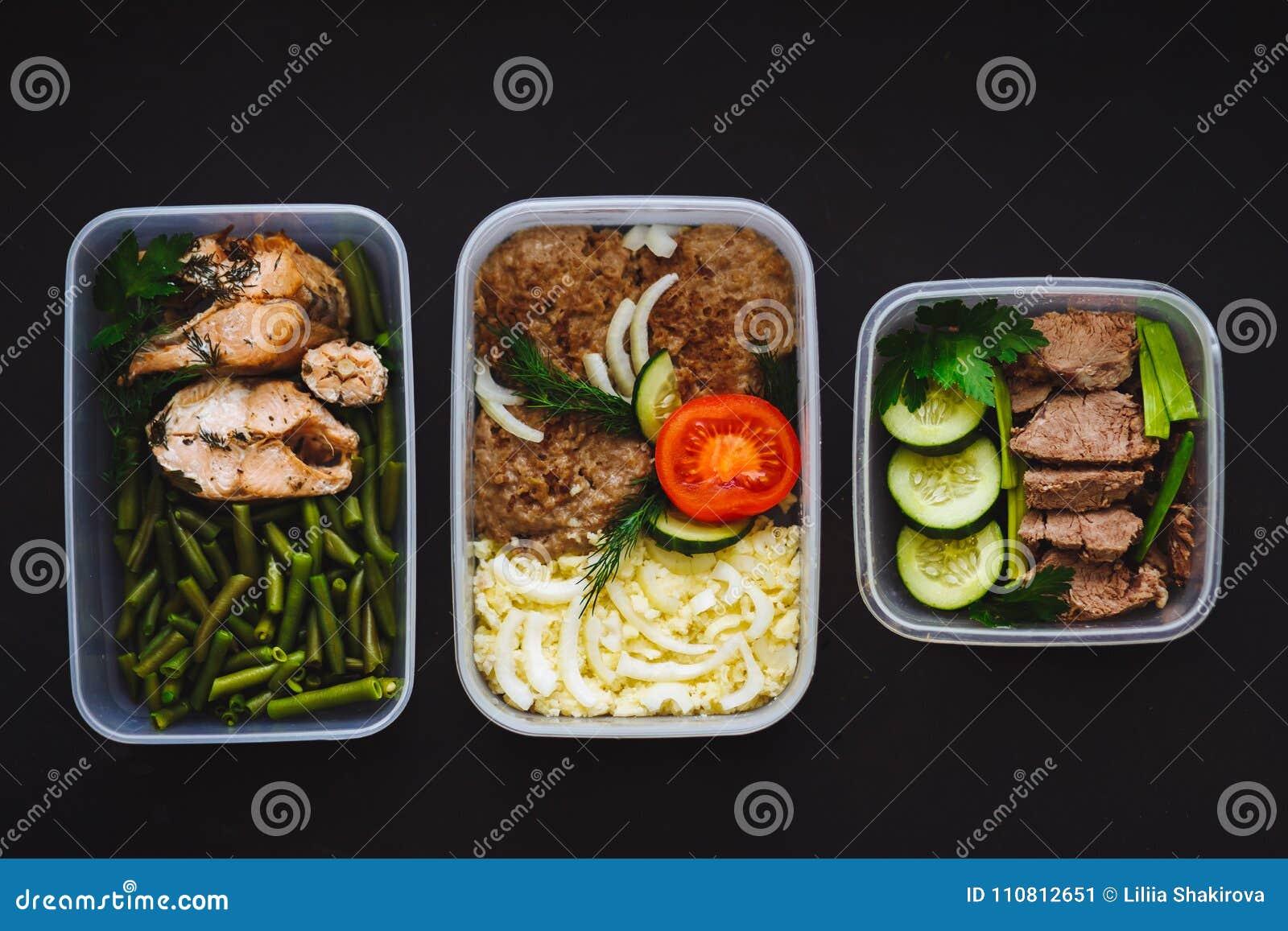 O alimento saudável nos recipientes no fundo preto: petisco, jantar, almoço Os peixes cozidos, feijões, costoletas da carne, trit