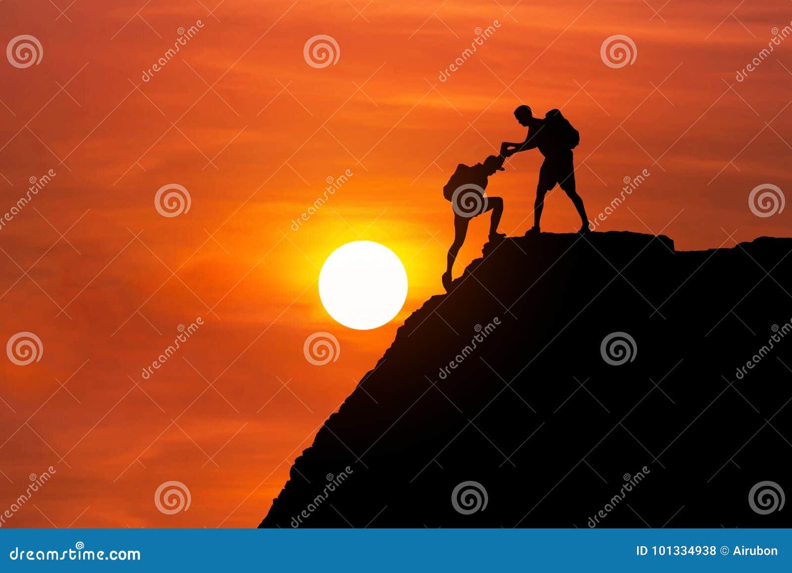 O alpinista da silhueta dá a mão amiga seu amigo para escalar junto a montanha alta do penhasco