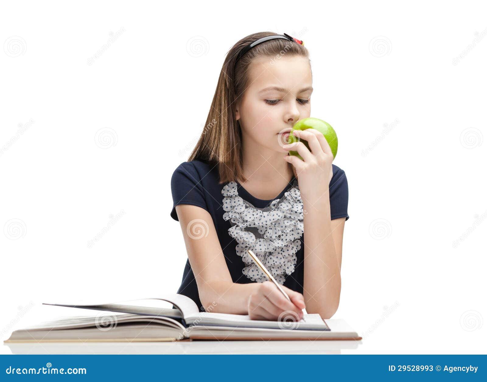 O aluno está comendo uma maçã madura