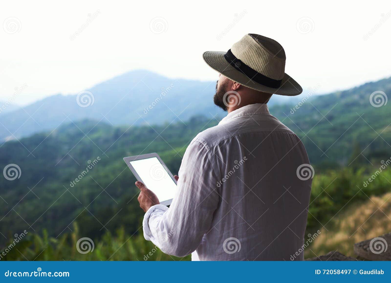 O andarilho masculino novo com a tabuleta digital nas mãos está apreciando o cenário maravilhoso das Amazonas